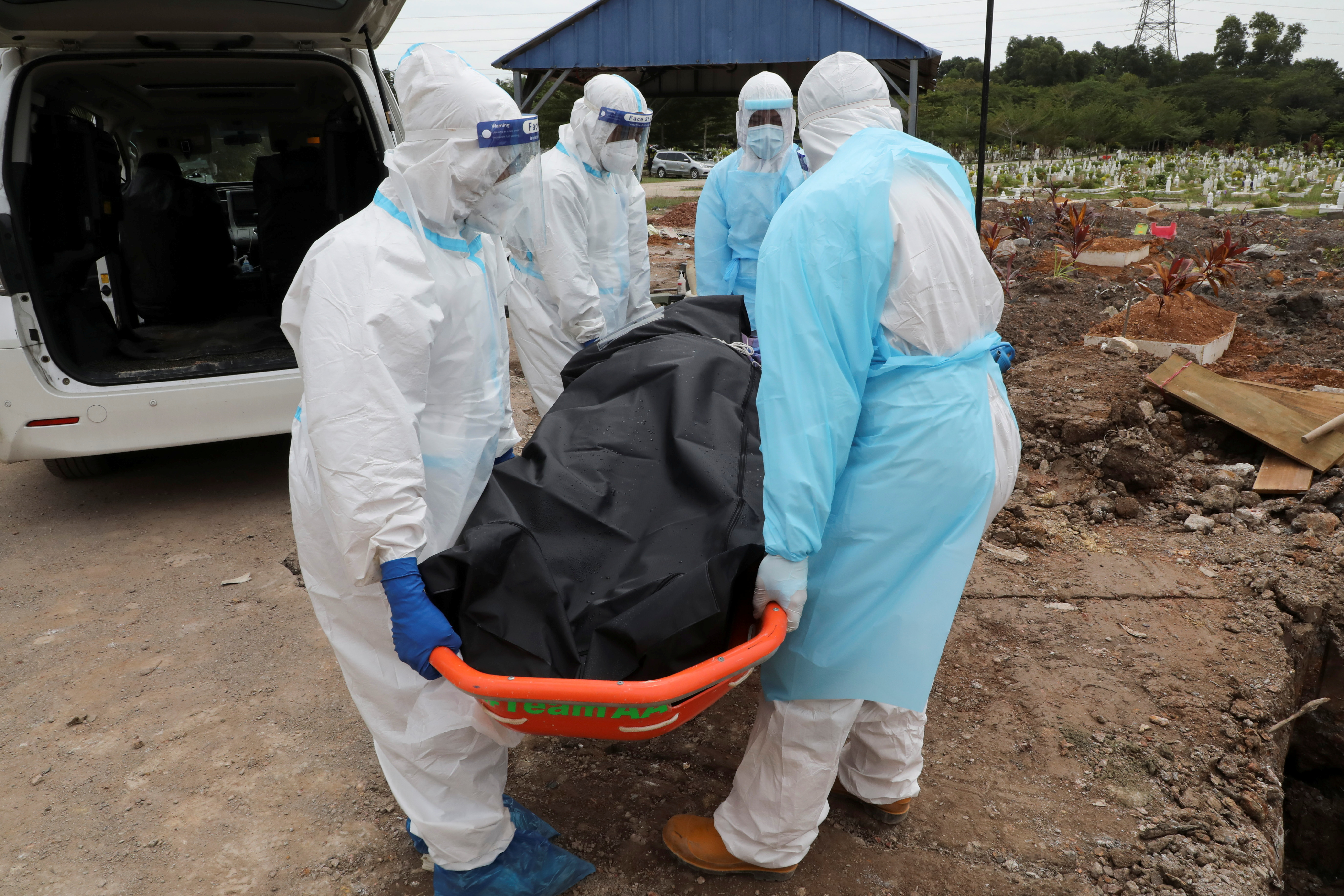 Cemetery workers wearing protective suits carry the body of a coronavirus disease (COVID-19) victim at a cemetery in Shah Alam, Malaysia, July 14, 2021. REUTERS/Lim Huey Teng