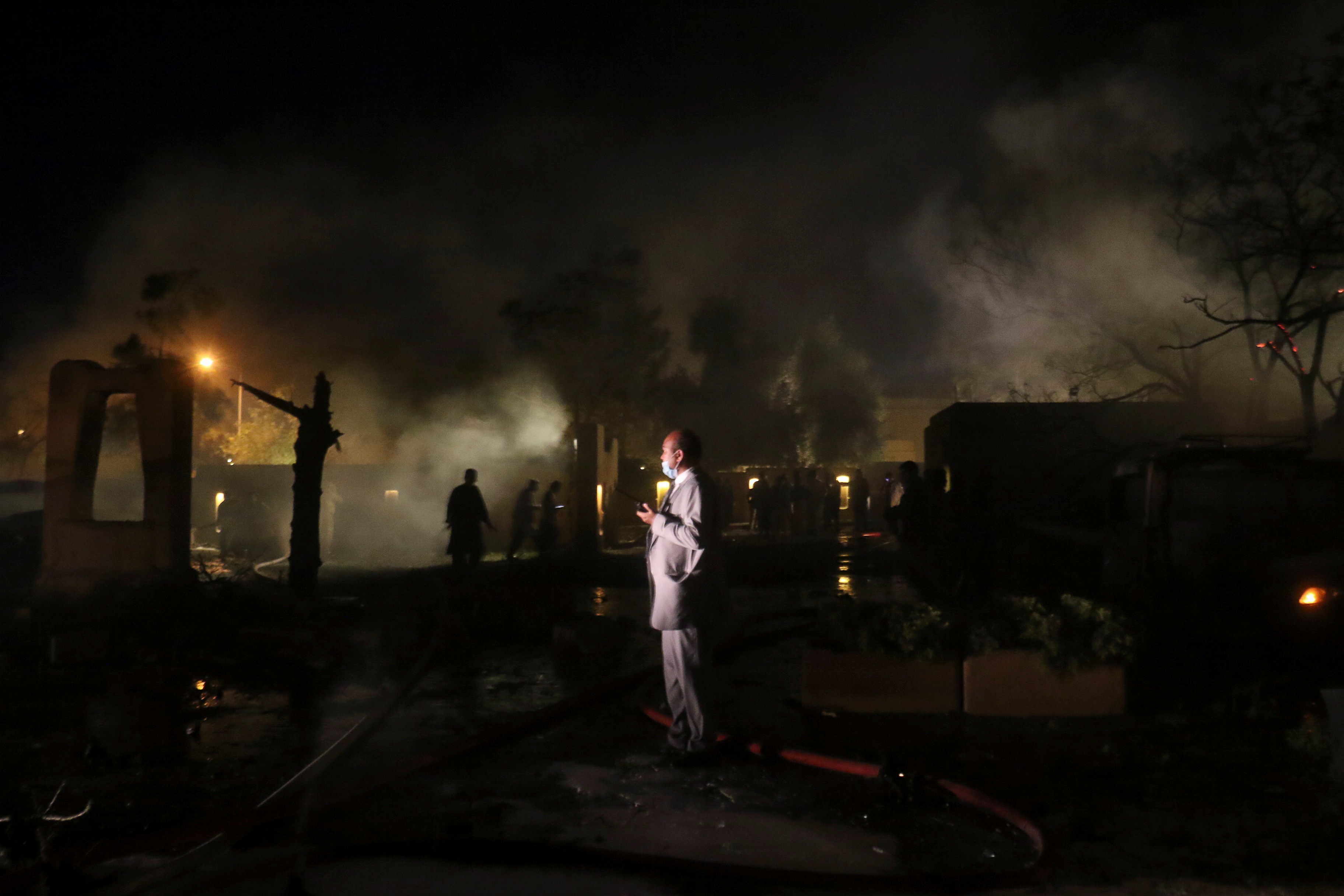A man uses a walkie talkie as he stands amid smoke from the burning vehicles after an explosion at a luxury hotel in Quetta, Pakistan April 21, 2021. REUTERS/Naseer Ahmed