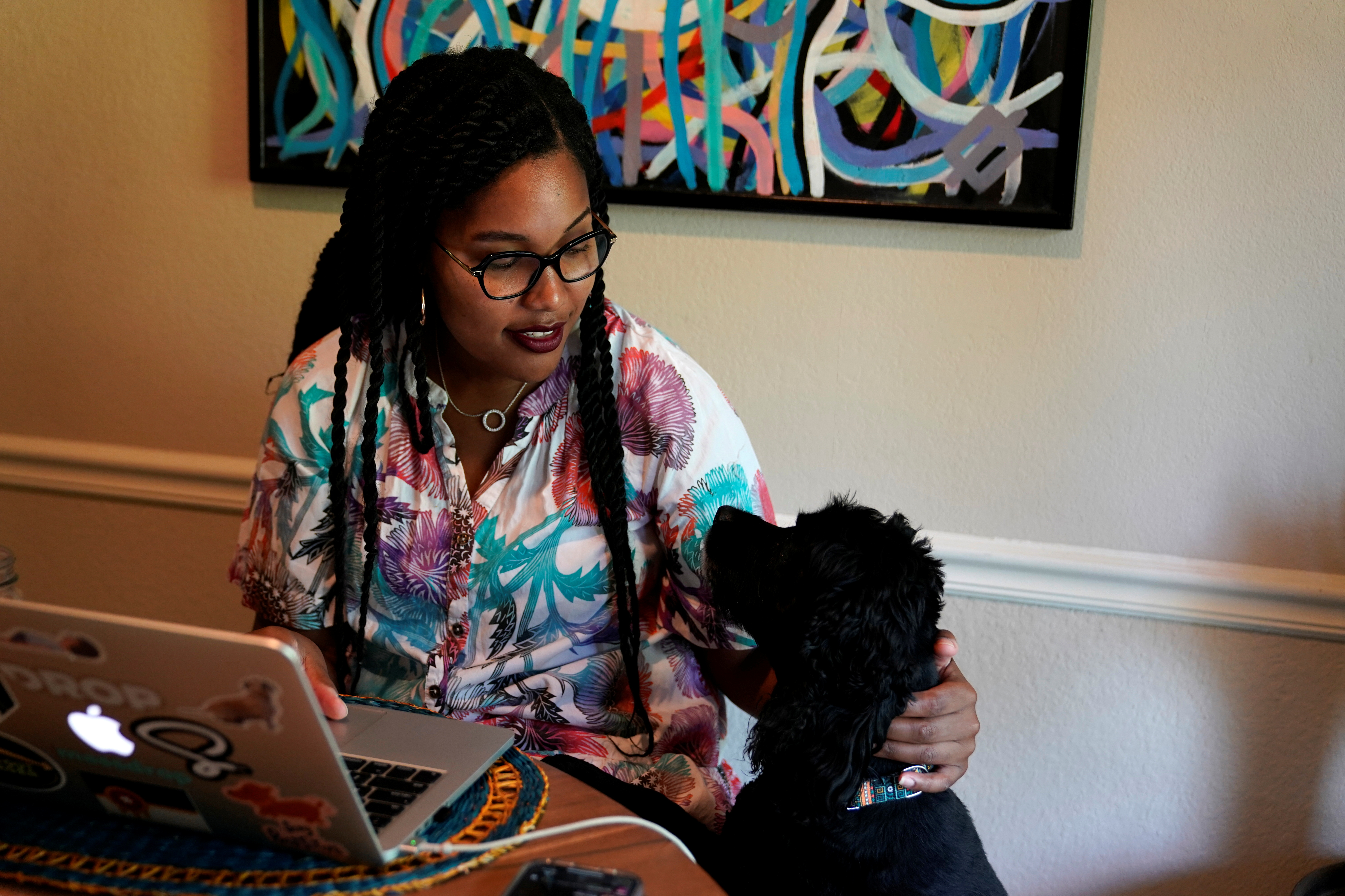 Jaleesa Garland, a marketing manager at an e-commerce startup who relocated from the Bay Area at the start of the COVID-19 pandemic, pets her dog Bo while working in her apartment in Tulsa, Oklahoma, U.S., July 9, 2021. REUTERS/Nick Oxford