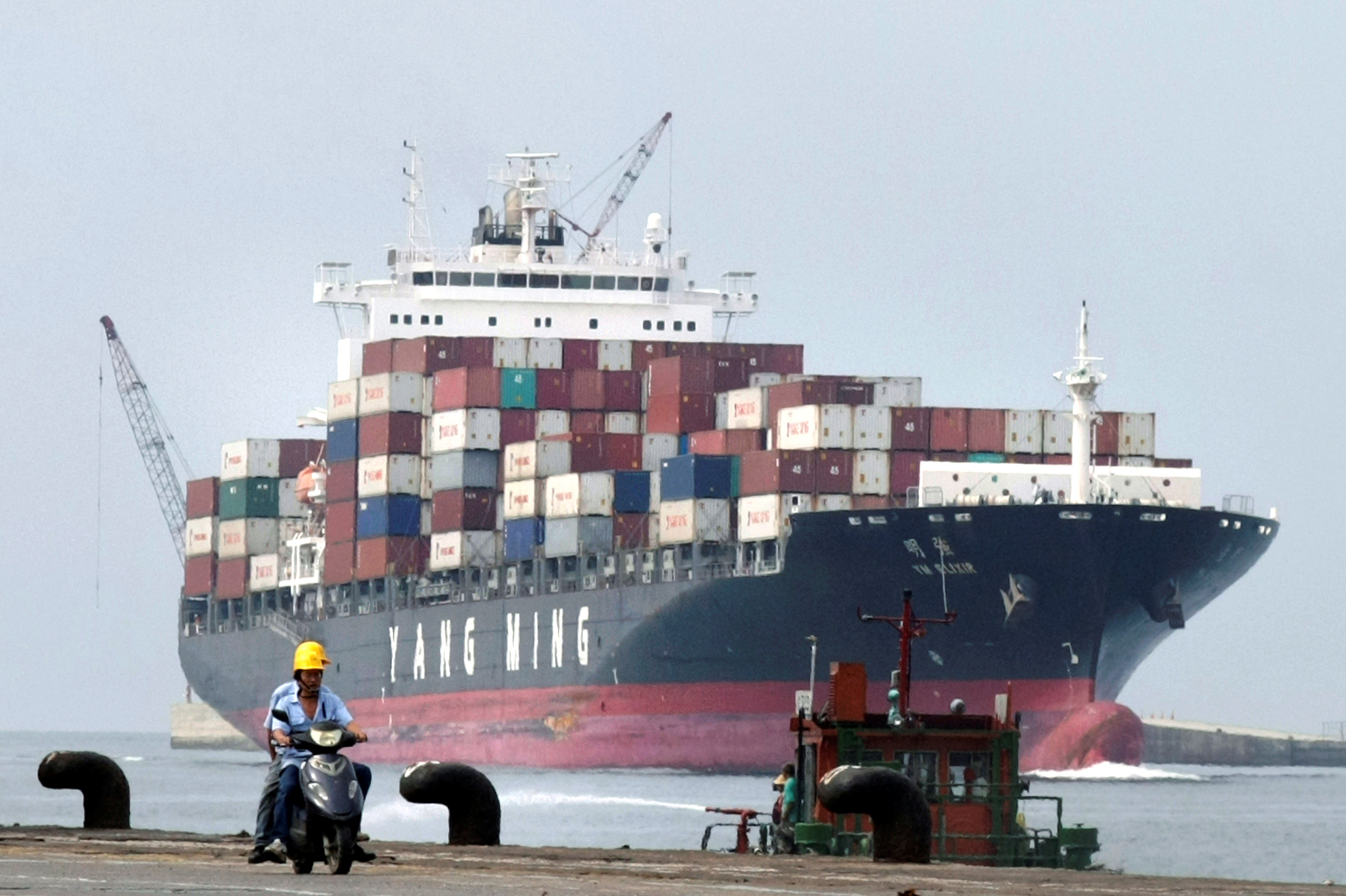 People ride a motorcycle while a container ship passes by at Keelung port in northern Taiwan July 20, 2010.   REUTERS/Pichi Chuang/File Photo