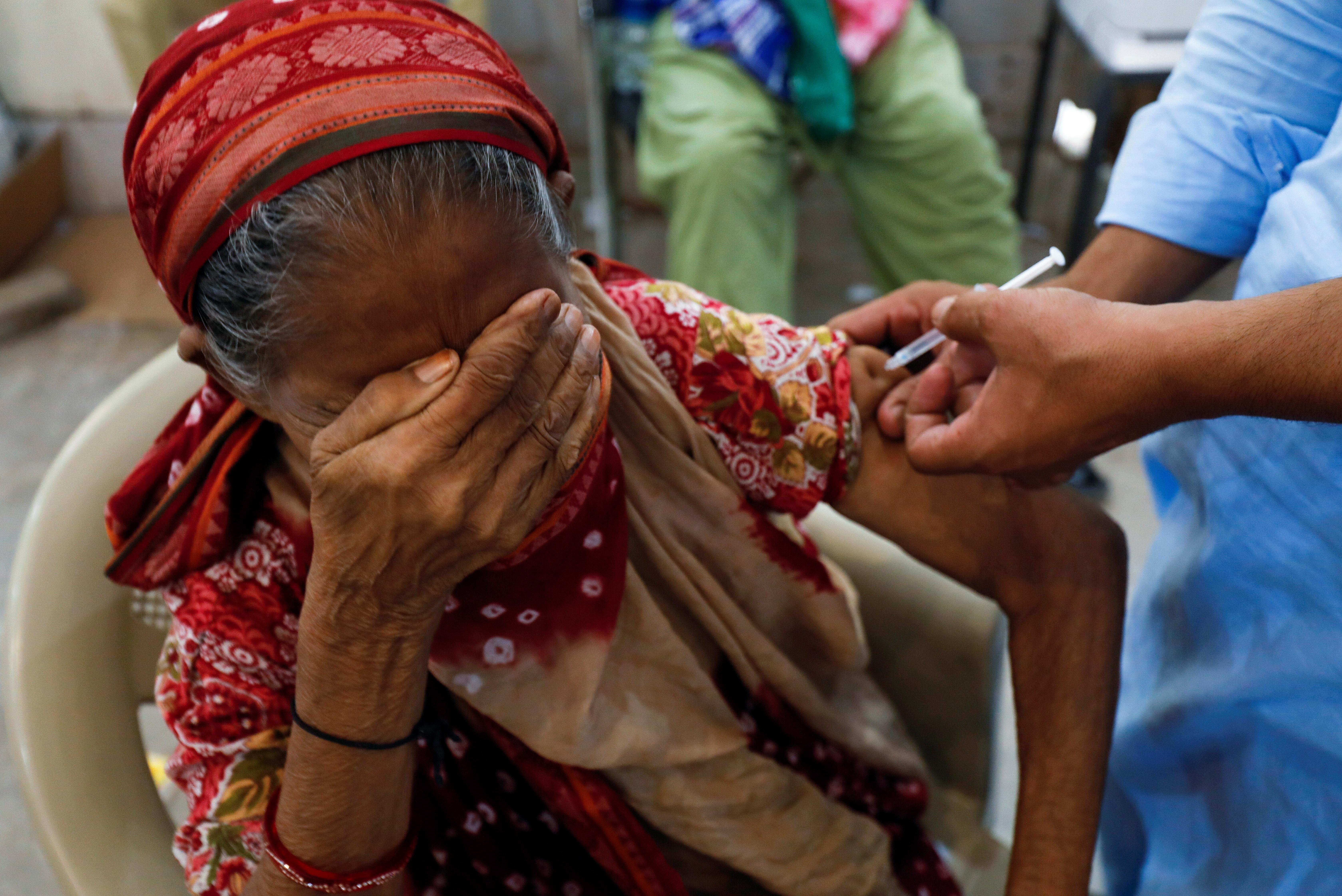 Basanti, 71, reacts as she receives a dose of the coronavirus disease (COVID-19) vaccine at a vaccination center in Karachi, Pakistan June 9, 2021. REUTERS/Akhtar Soomro