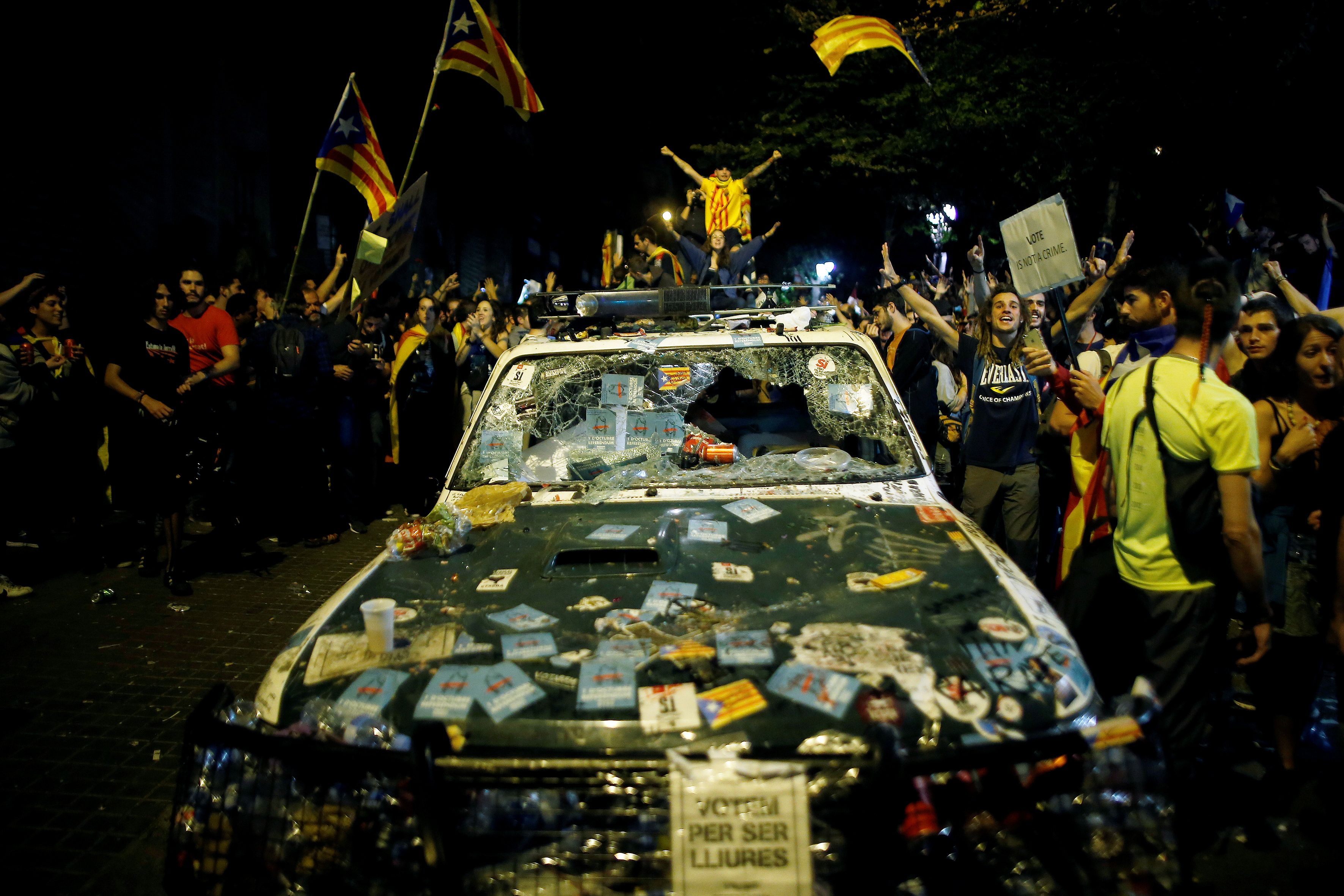 Οι διαδηλωτές φωνάζουν συνθήματα δίπλα σε ένα χαλασμένο περιπολικό της Ισπανικής Αστυνομίας έξω από το κτίριο του υπουργείου οικονομίας της καταλανικής περιοχής κατά τη διάρκεια επιδρομής της ισπανικής αστυνομίας σε κυβερνητικά γραφεία, στη Βαρκελώνη της Ισπανίας, στις 21 Σεπτεμβρίου 2017. REUTERS / Jon Nazca