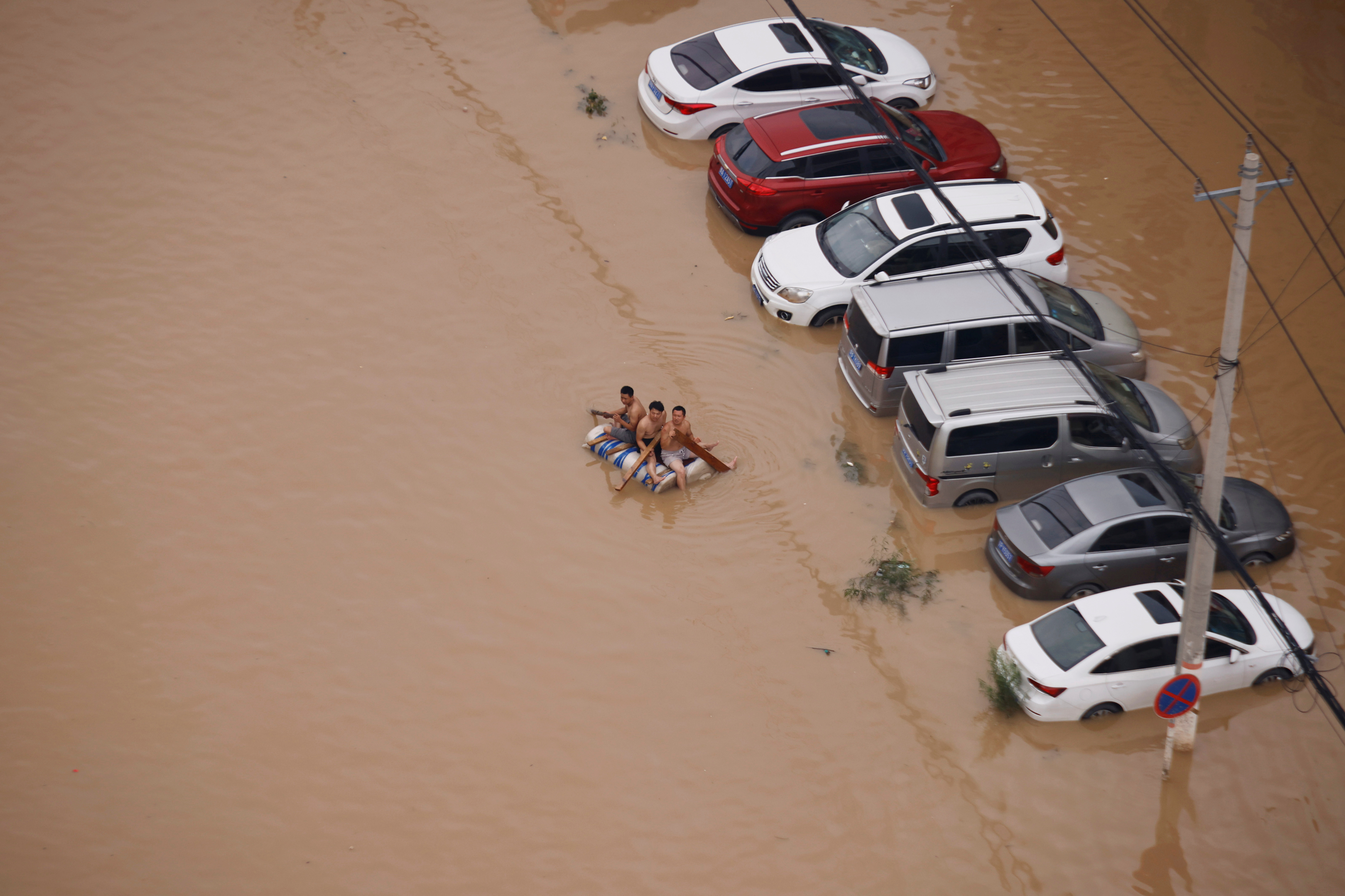 People on a makeshift raft make their way through a flooded road following heavy rainfall in Zhengzhou, Henan province, China July 22, 2021.  REUTERS/Aly Song