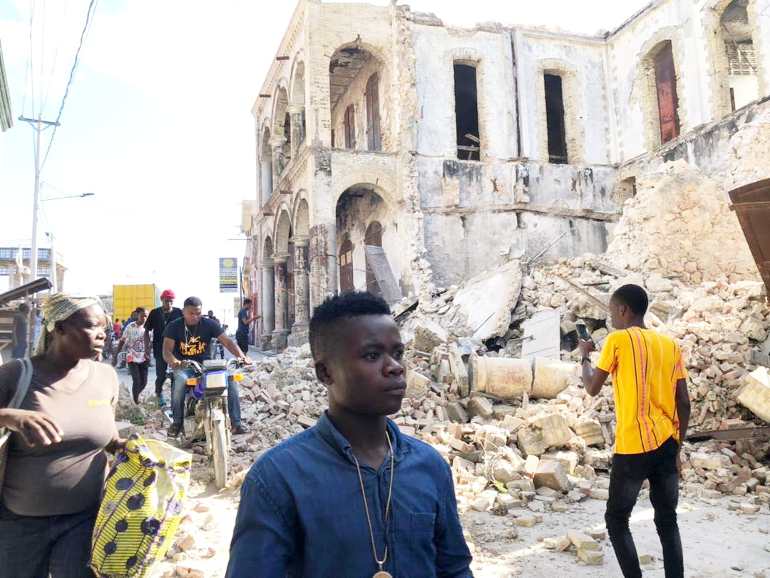 People walk along the street next to destroyed buildings following an earthquake in Jeremie, Haiti August 14, 2021, in this picture obtained from social media. Courtesy of TWITTER @JCOMHaiti/ via REUTERS ATTENTION EDITORS - THIS IMAGE HAS BEEN SUPPLIED BY A THIRD PARTY. MANDATORY CREDIT. MUST NOT OBSCURE LOGO