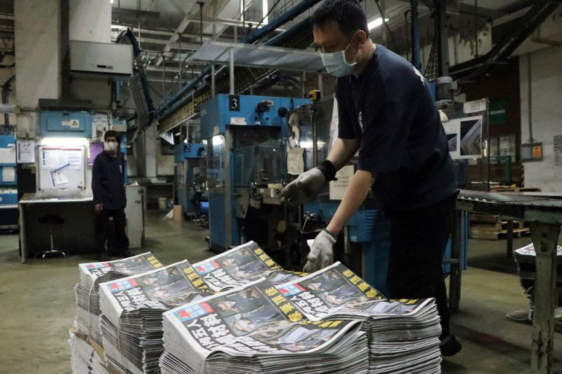 Employees work at the printing facility of Apple Daily newspaper after police raided its newsroom and arrested five executives, in Hong Kong, China early June 18, 2021. REUTERS/Jessie Pang