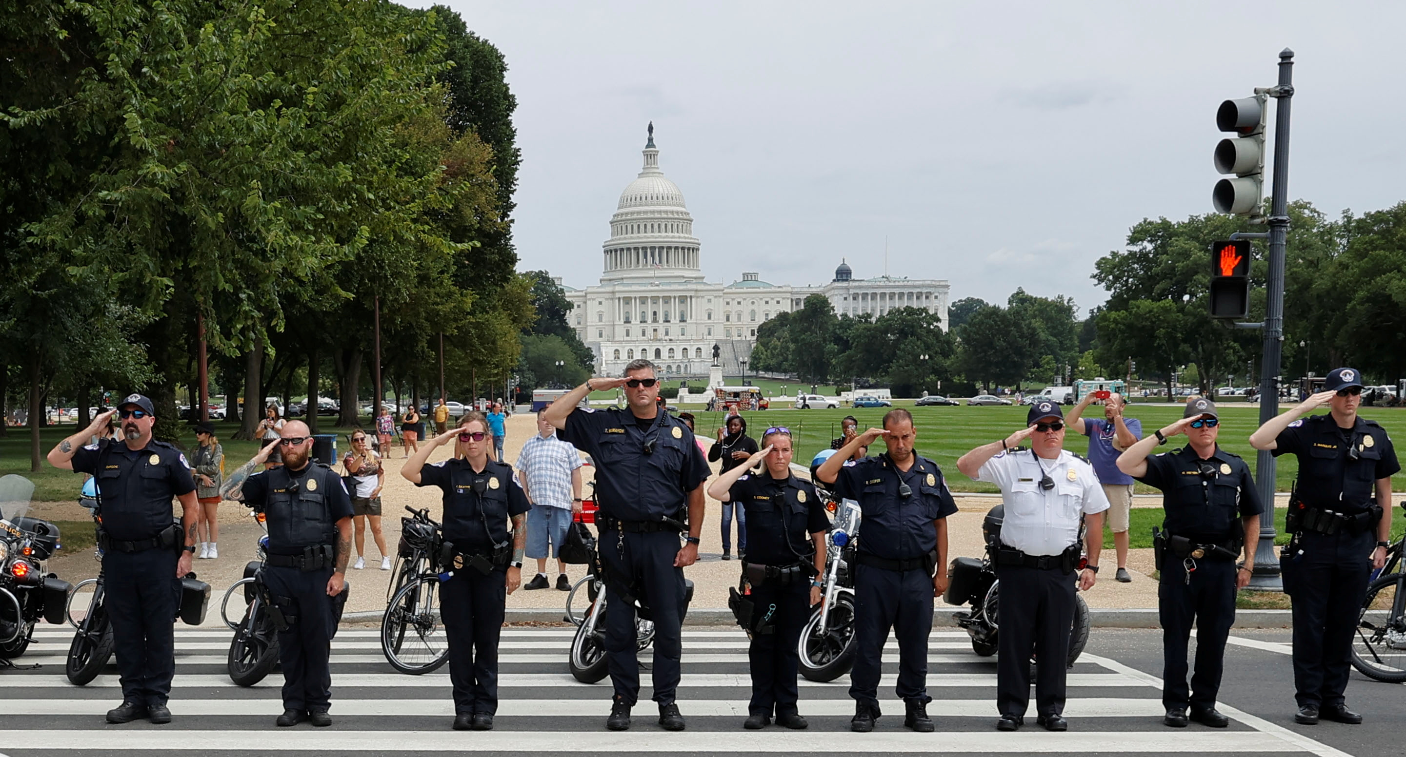 Law enforcement officers from Washington's Metropolitan Police Department, the U.S. Capitol Police, the Pentagon Force Protection Agency and other police departments salute as a ceremonial procession in honor of a police officer wounded in a shooting at the Pentagon earlier in the day passes the U.S. Capitol in Washington, August 3, 2021.  REUTERS/Jim Bourg