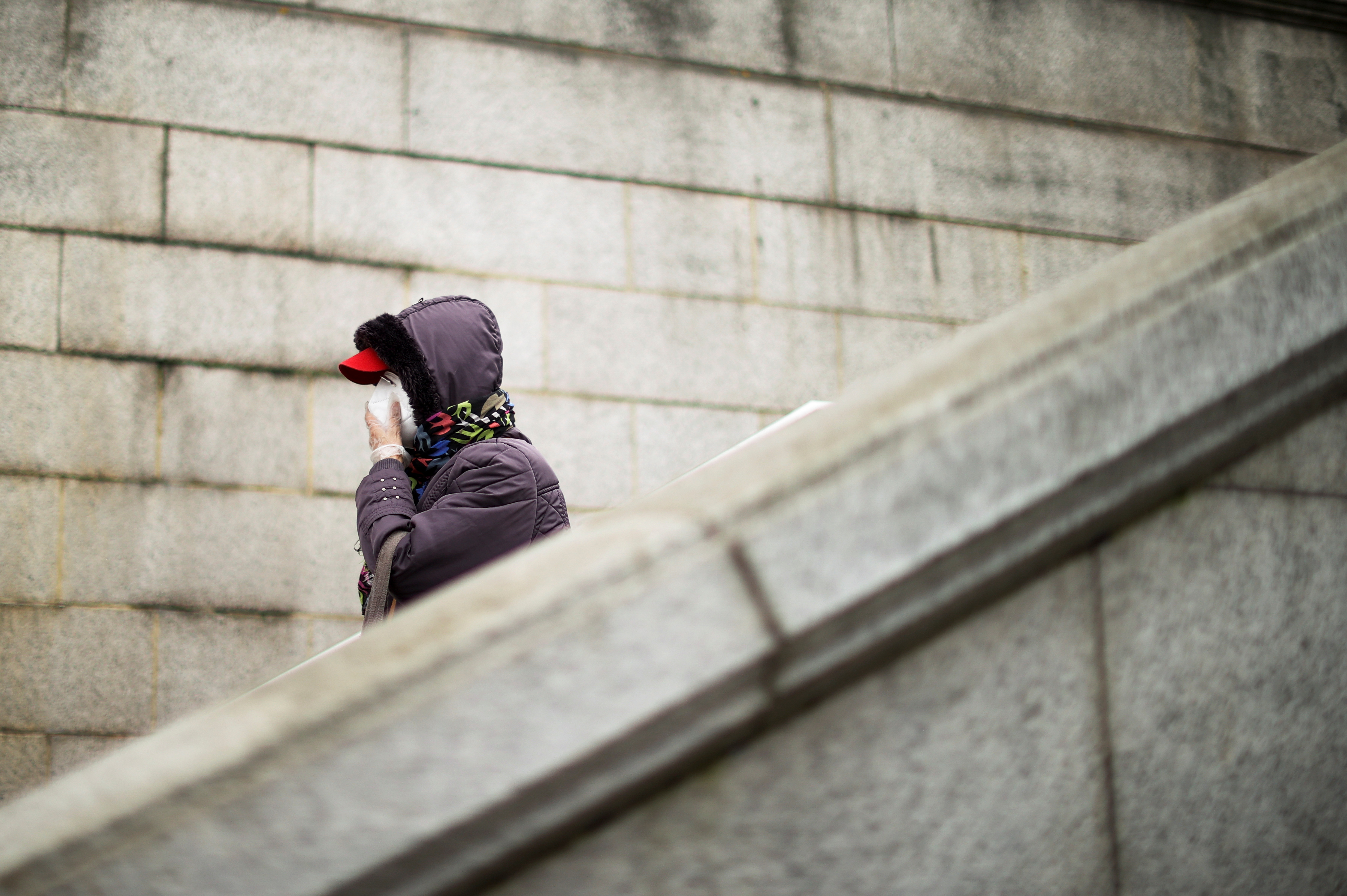 A person wearing a face mask and gloves walks down the stairs, amid the coronavirus disease (COVID-19) outbreak, in London, Britain February 22, 2021. REUTERS/Hannah McKay