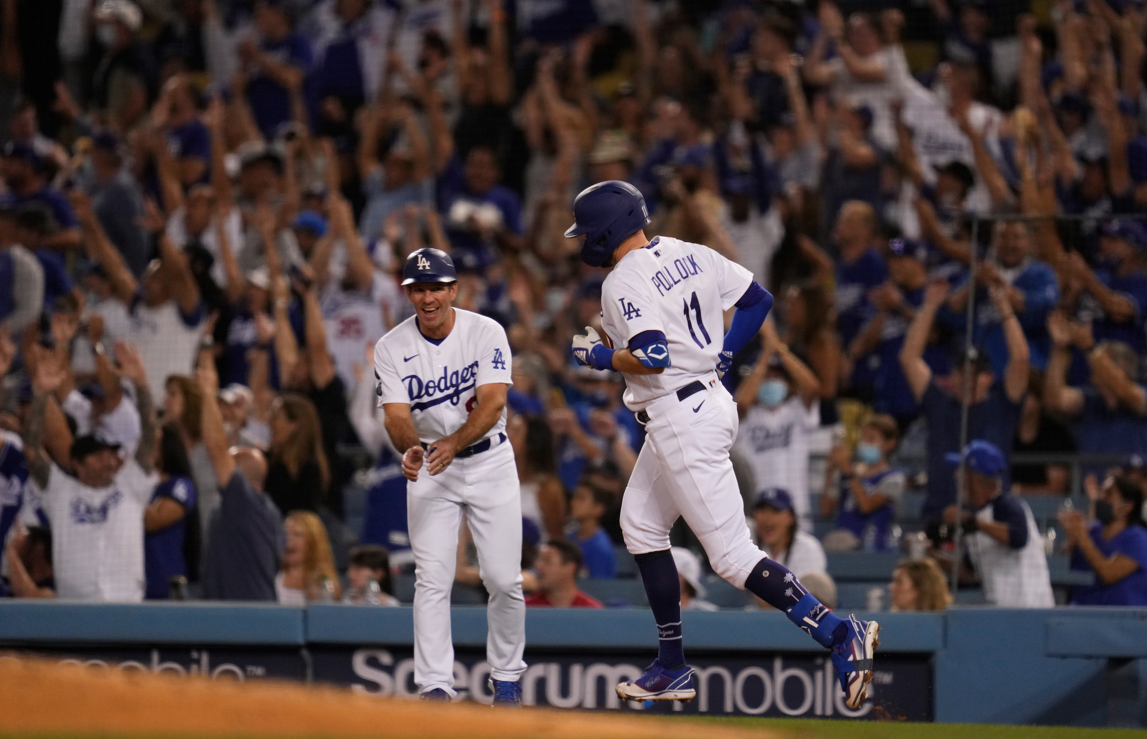 Oct 2, 2021; Los Angeles, California, USA; Los Angeles Dodgers left fielder AJ Pollock (11) rounds the bases after hitting a two run home run against the Milwaukee Brewers in the fourth inning at Dodger Stadium. Los Angeles Dodgers first base coach Clayton McCullough (86) claps as Pollock approaches first base. Mandatory Credit: Robert Hanashiro-USA TODAY Sports