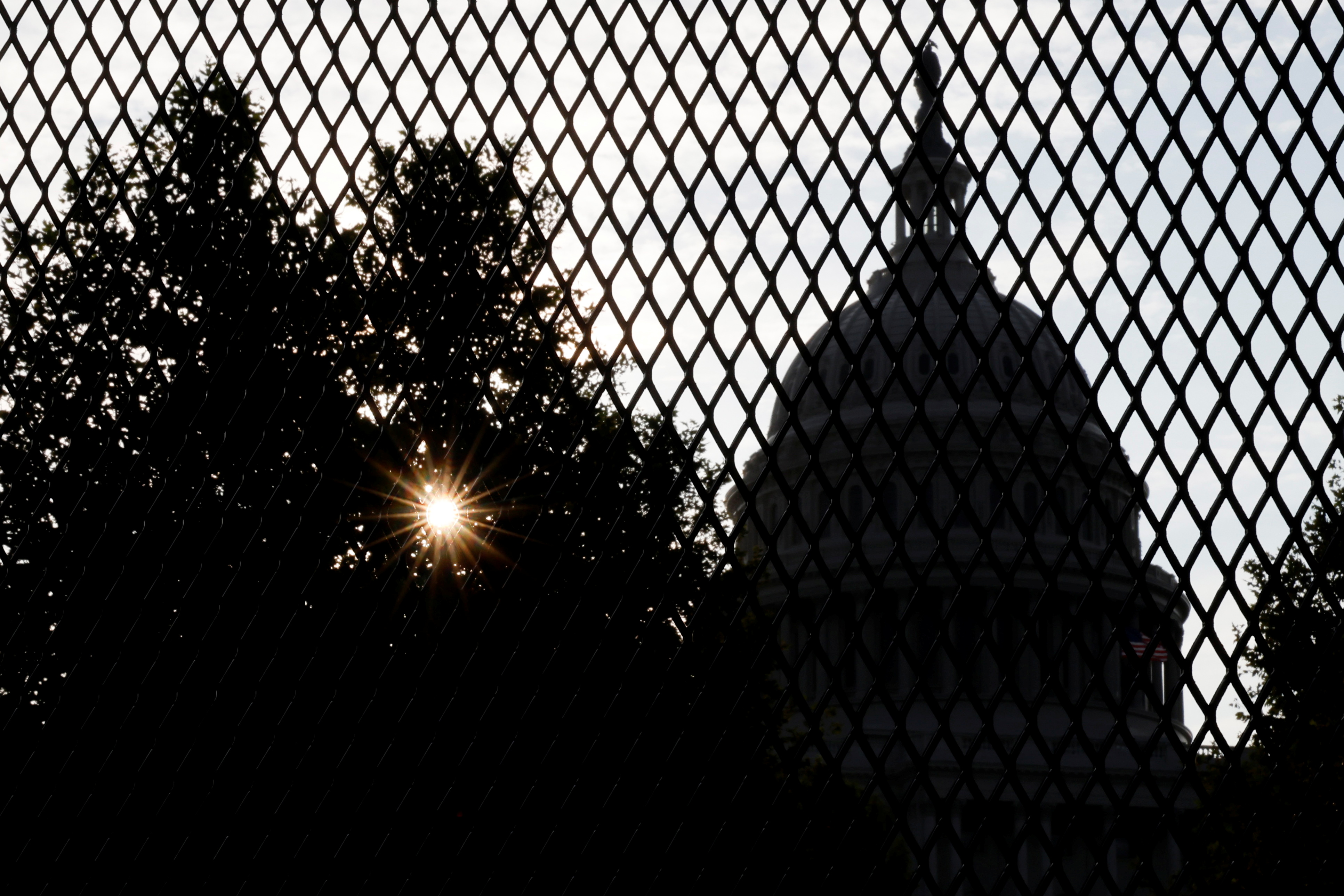 The sun rises behind the U.S. Capitol, surrounded by a security fence ahead of an expected rally Saturday in support of the Jan. 6 defendants in Washington, U.S. September 16, 2021.  REUTERS/Jonathan Ernst
