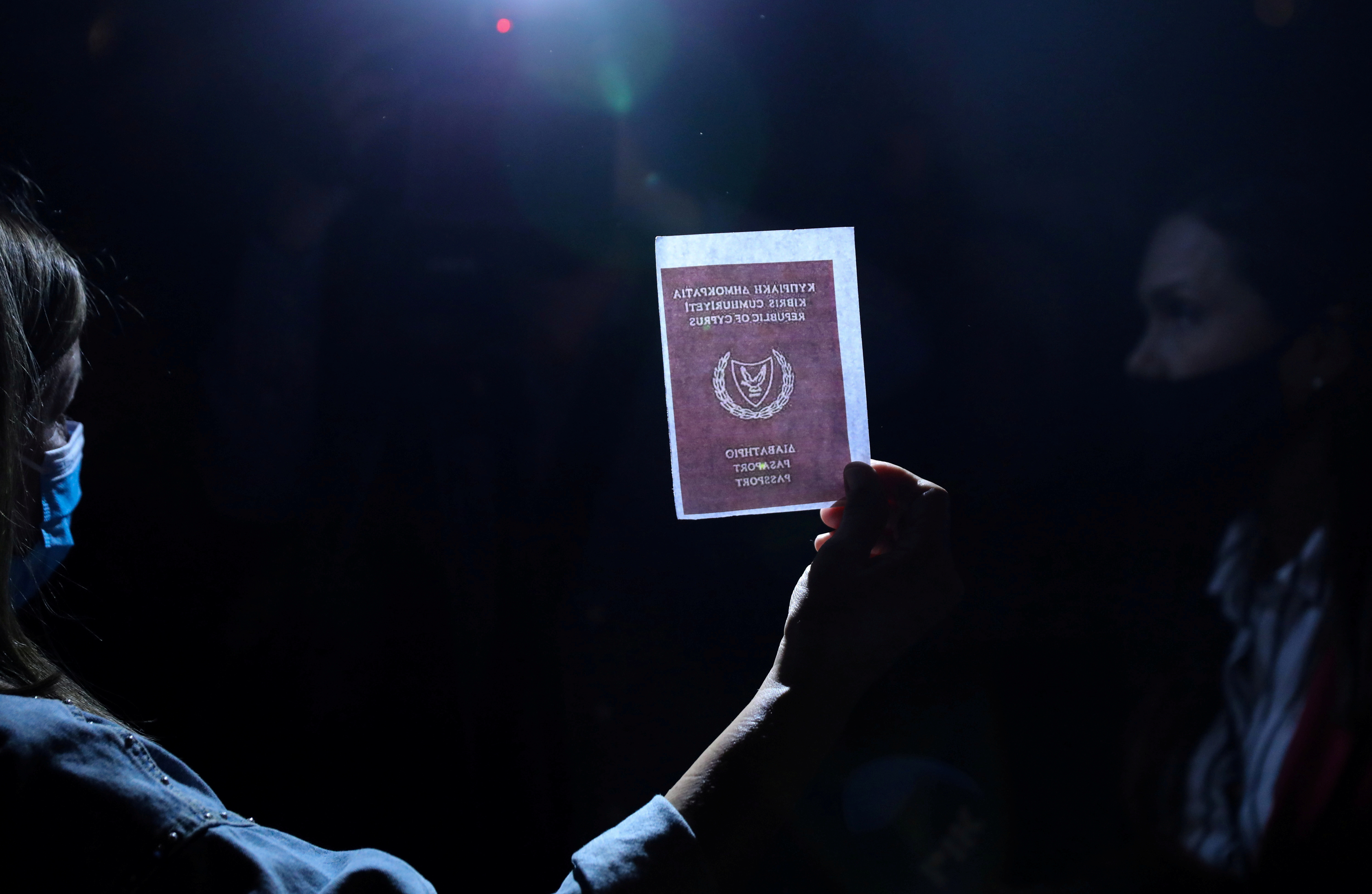 A person holds an image of a passport during a protest against corruption outside the Filoxenia Conference Center, currently hosting Cyprus parliament, in Nicosia, Cyprus October 14, 2020. REUTERS/Yiannis Kourtoglou