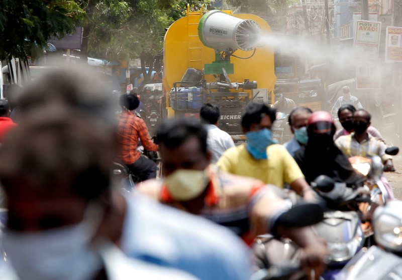 People wearing face maks ride motorcycles as a municipal vehicle decontaminates a road during a 21-day nationwide lockdown to slow the spreading of coronavirus disease (COVID-19), in Chennai, India, April 9, 2020. REUTERS/P. Ravikumar/File Photo