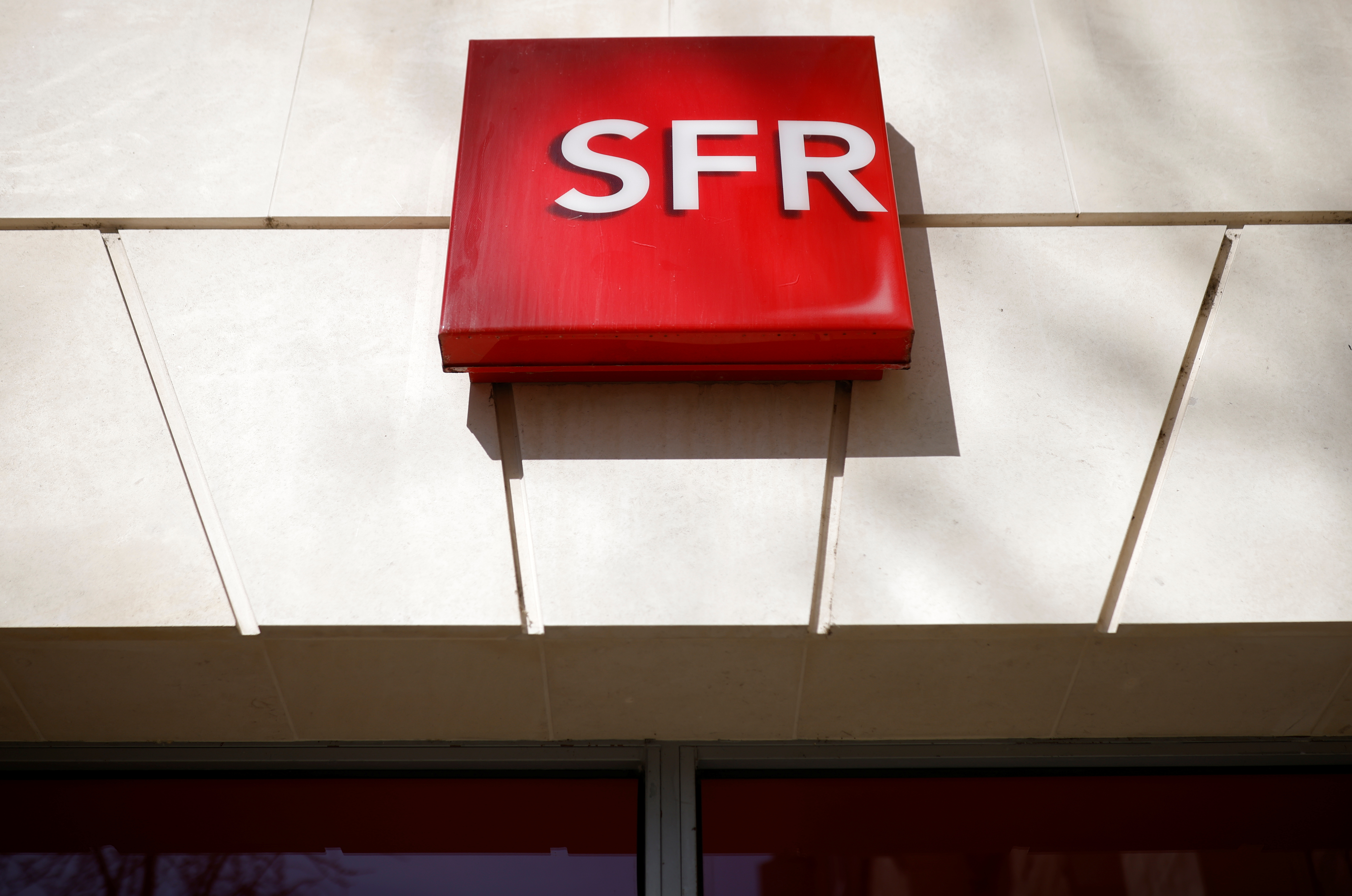 The logo of French telecoms operator SFR is pictured on a shop in Niort, France, March 4, 2021. REUTERS/Stephane Mahe