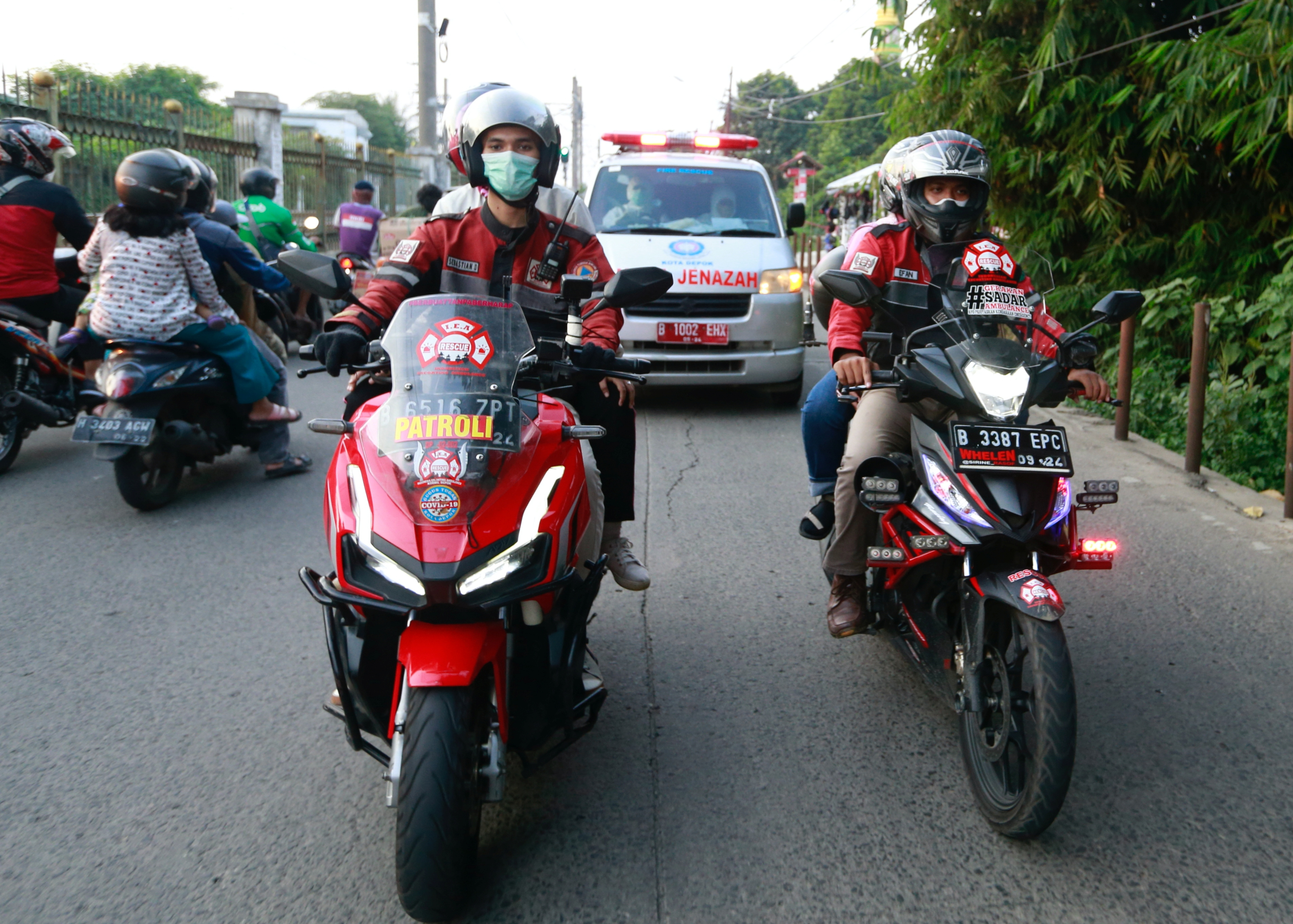 Volunteer bikers escort an ambulance to a cemetery as coronavirus disease (COVID-19) cases surge in Depok on the outskirts of Jakarta, Indonesia, July 2, 2021. REUTERS/Ajeng Dinar Ulfiana
