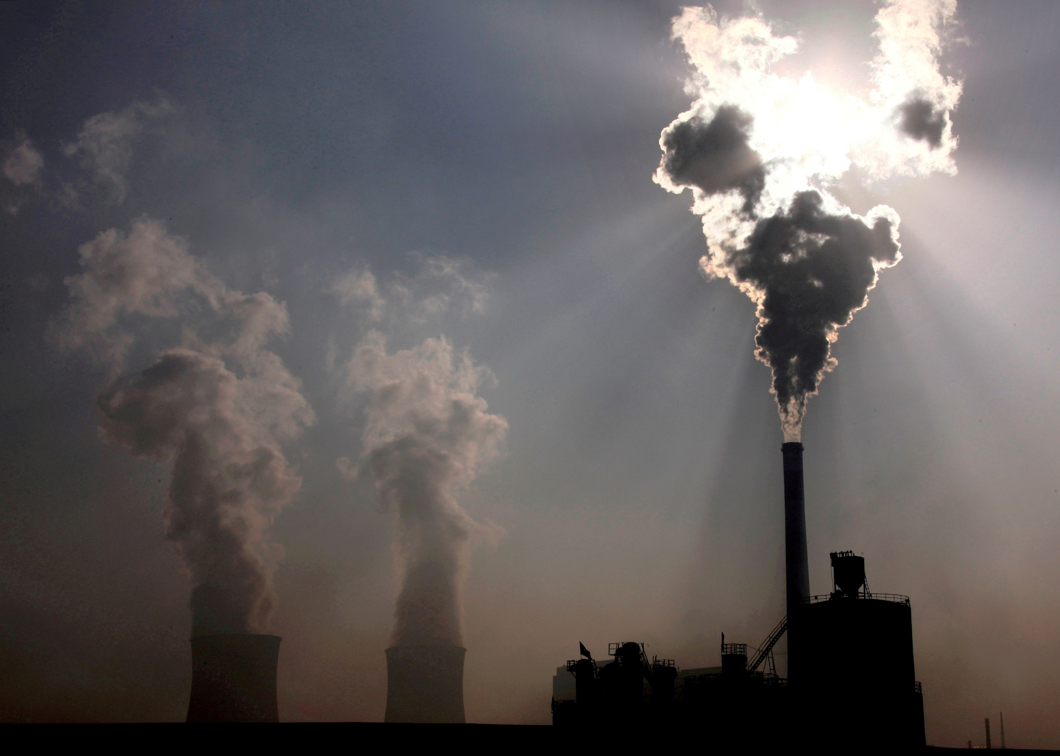 A coal-burning power plant can be seen behind a factory in China's Inner Mongolia Autonomous Region, October 31, 2010.  REUTERS/David Gray