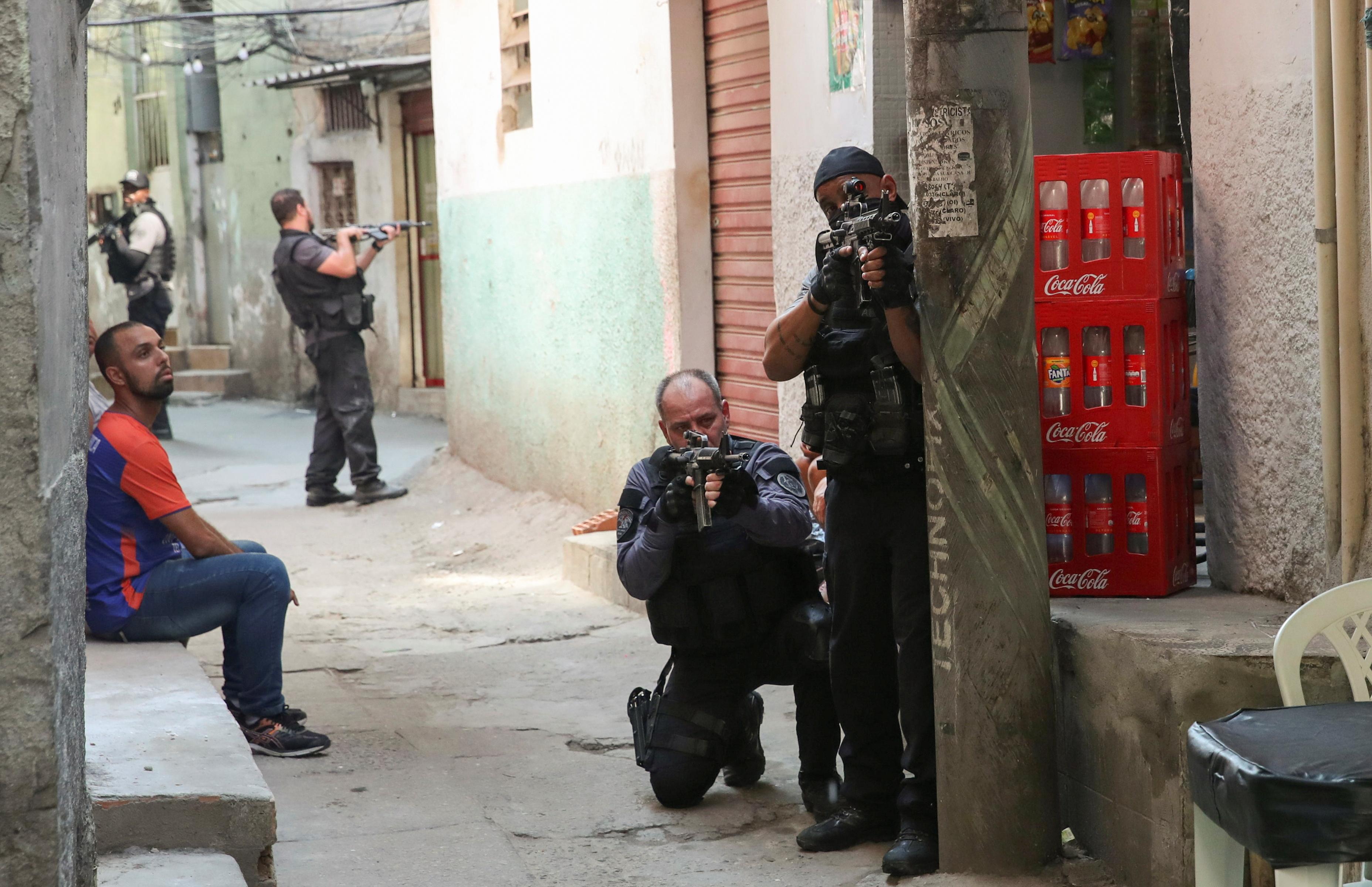 Policemen aim their weapons during an operation against drug dealers in Jacarezinho slum in Rio de Janeiro, Brazil May 6, 2021. REUTERS/Ricardo Moraes