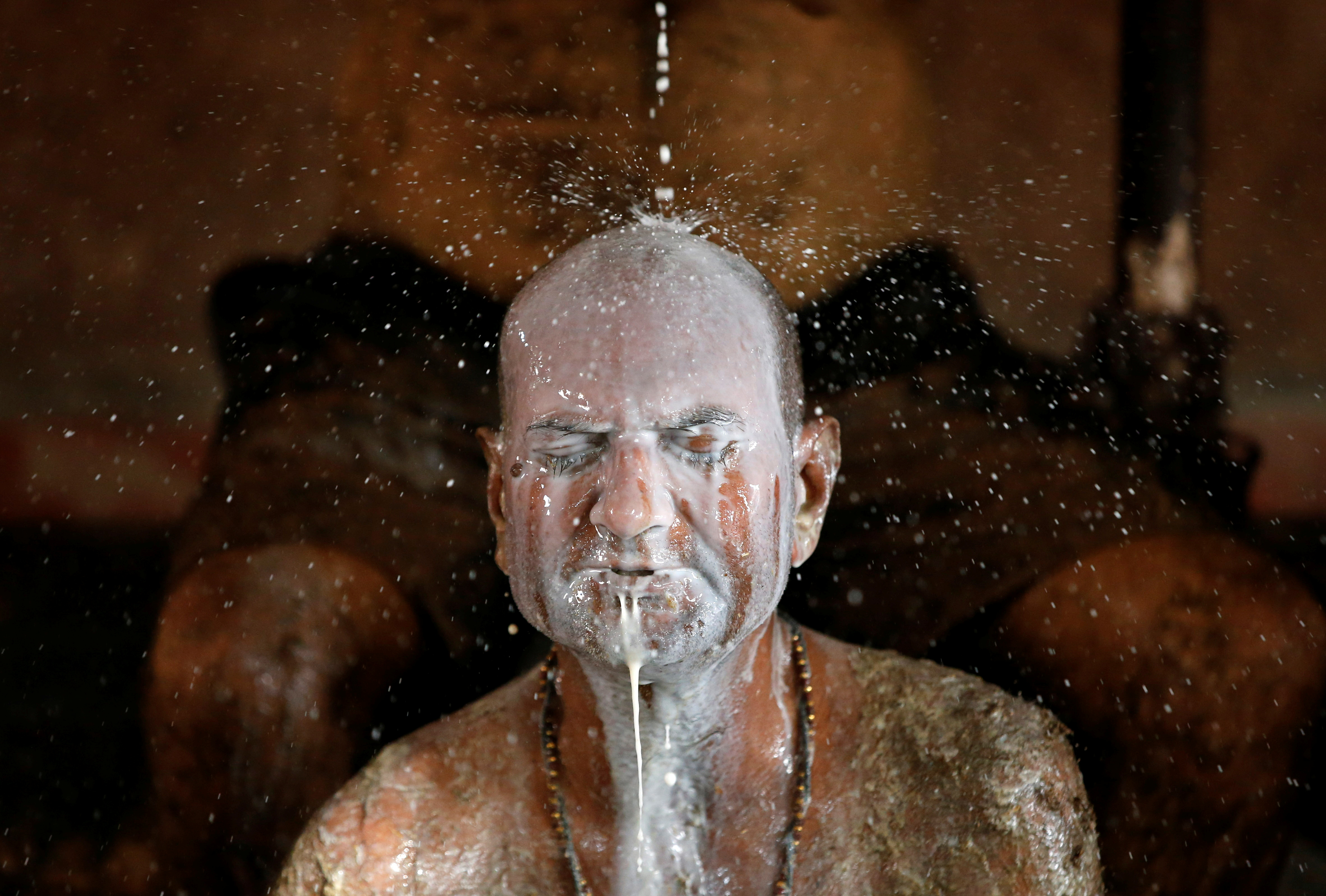 """Ashok Oza bathes in cow milk to remove cow dung from his body during """"cow dung therapy"""", believing it will boost his immunity to defend against the coronavirus disease (COVID-19) at the Shree Swaminarayan Gurukul Vishwavidya Pratishthanam Gaushala or cow shelter on the outskirts of Ahmedabad, India, May 9, 2021. REUTERS/Amit Dave"""