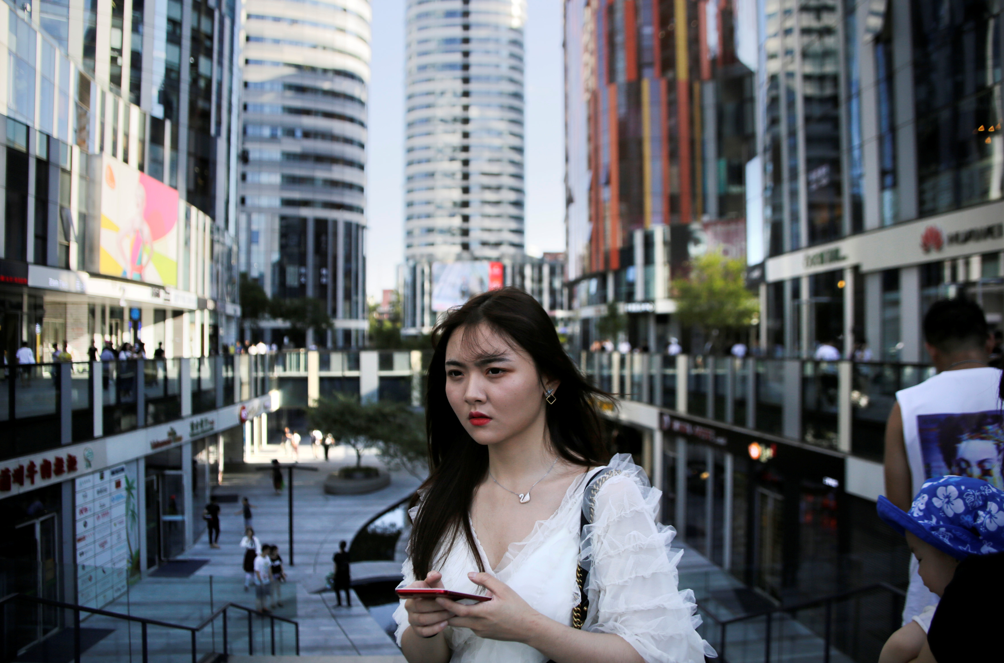 A young woman walks at Sanlitun Soho residential and commercial complex in Beijing, China June 28, 2018. REUTERS/Jason Lee