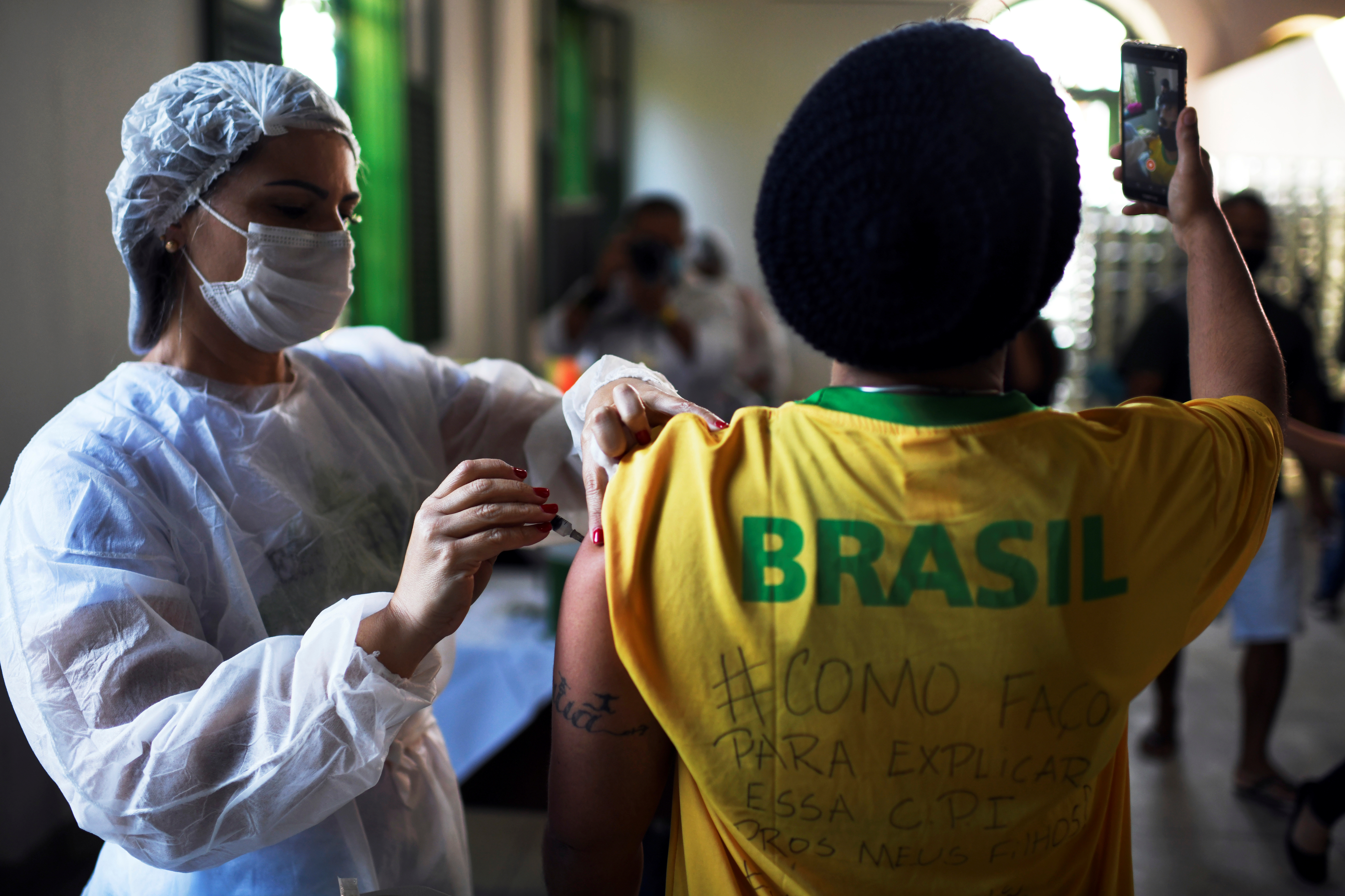 A health worker administers a dose of Johnson & Johnson vaccine against the coronavirus disease (COVID-19) to a resident as he takes a selfie, during mass vaccination at the Ilha Grande island, one of the most famous tourist spots in Rio de Janeiro state, Brazil, July 10, 2021. REUTERS/Lucas Landau