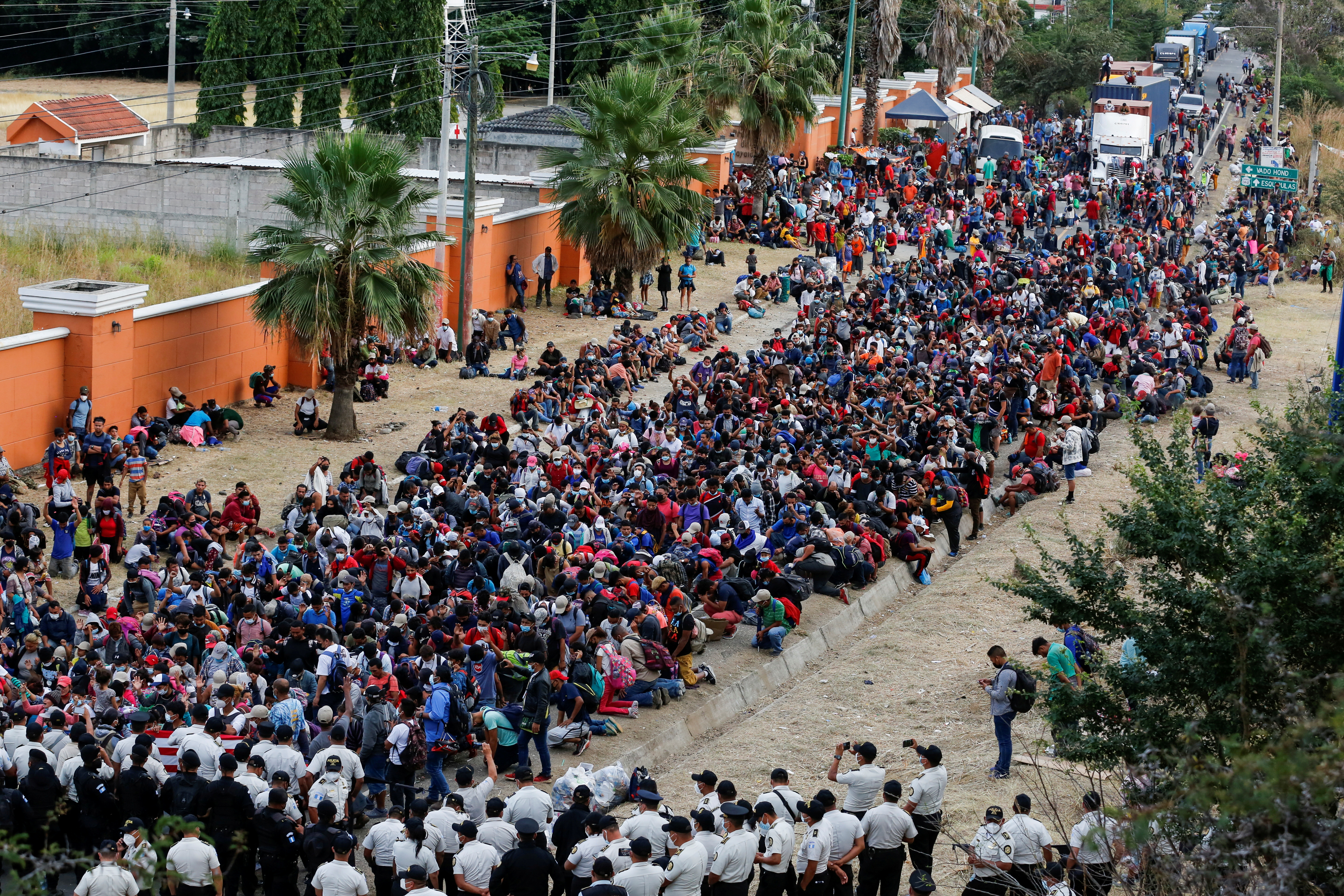 Hondurans taking part in a new caravan of migrants, set to head to the United States, gather in front of police officers blocking the road in Vado Hondo, Guatemala January 17, 2021. REUTERS/Luis Echeverria