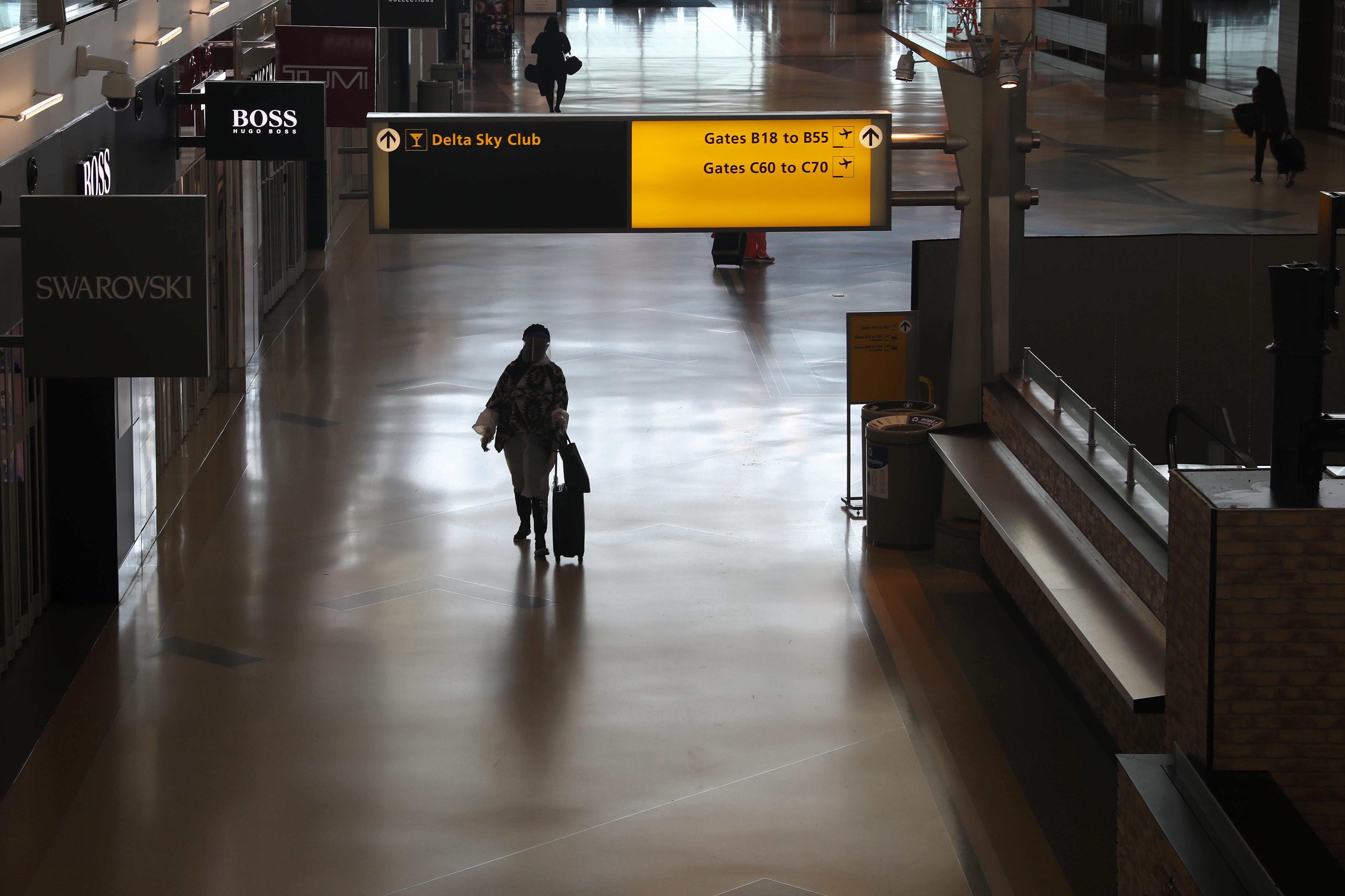 Air travelers walk through a terminal as the coronavirus disease (COVID-19) outbreak continues, at New York's JFK International Airport in New York, U.S., May 15, 2020. REUTERS/Shannon Stapleton