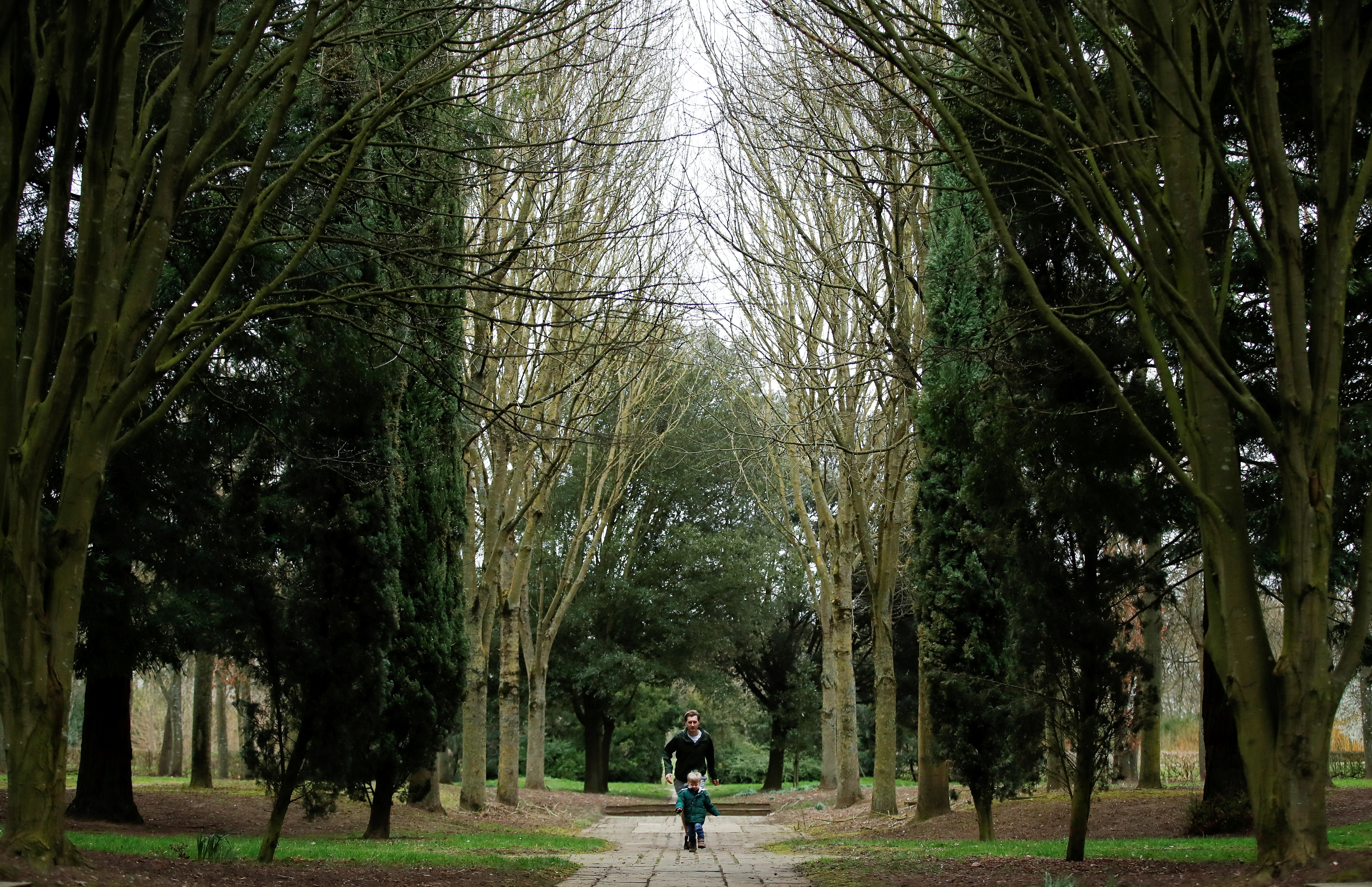 A family plays while walking through the Tree Cathedral in Milton Keynes, Britain. March 18, 2021. REUTERS/Andrew Boyers/File Photo