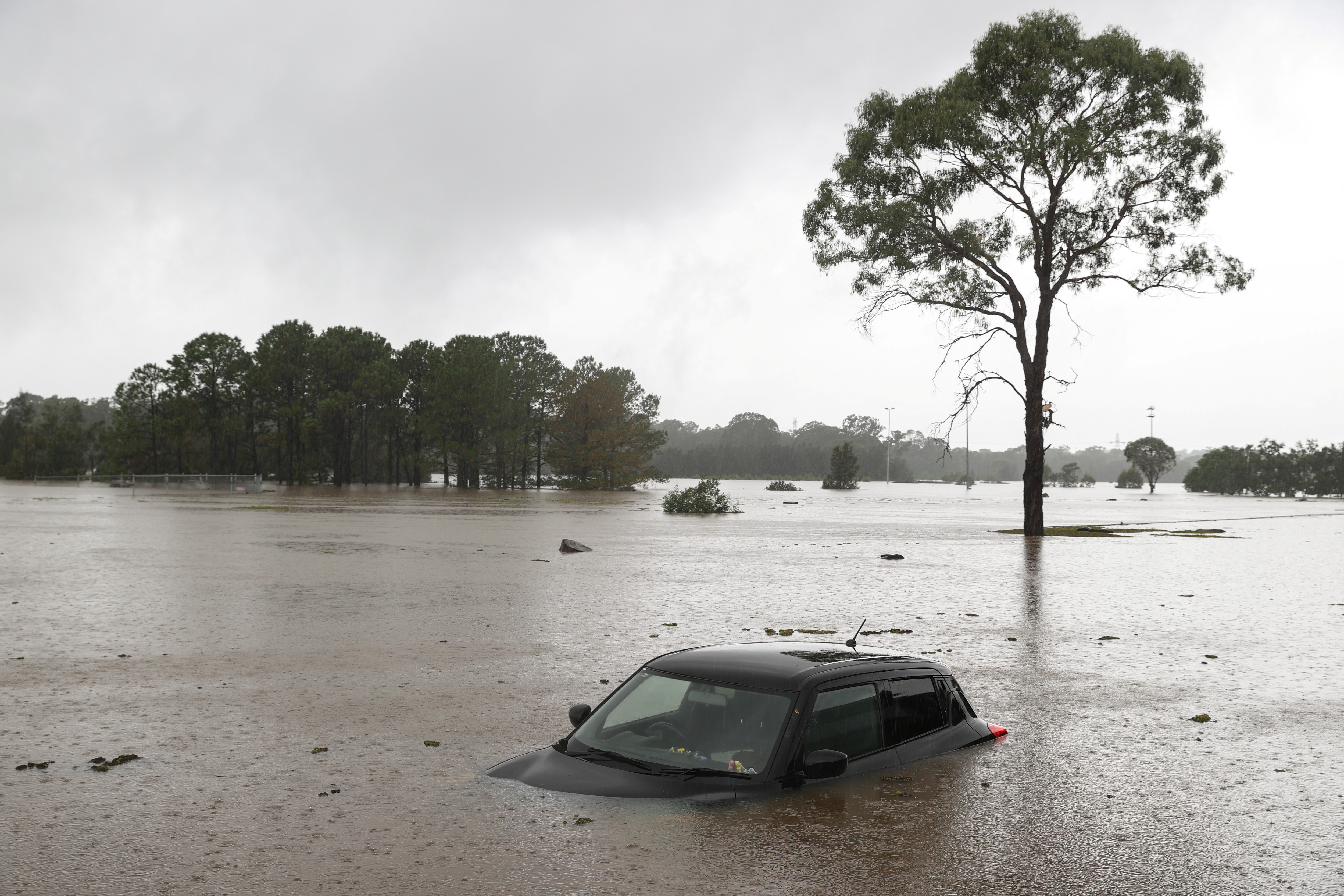 A partially submerged car is seen abandoned in floodwaters in the suburb of Windsor as the state of New South Wales experiences widespread flooding and severe weather, in Sydney, Australia, March 22, 2021.  REUTERS/Loren Elliott