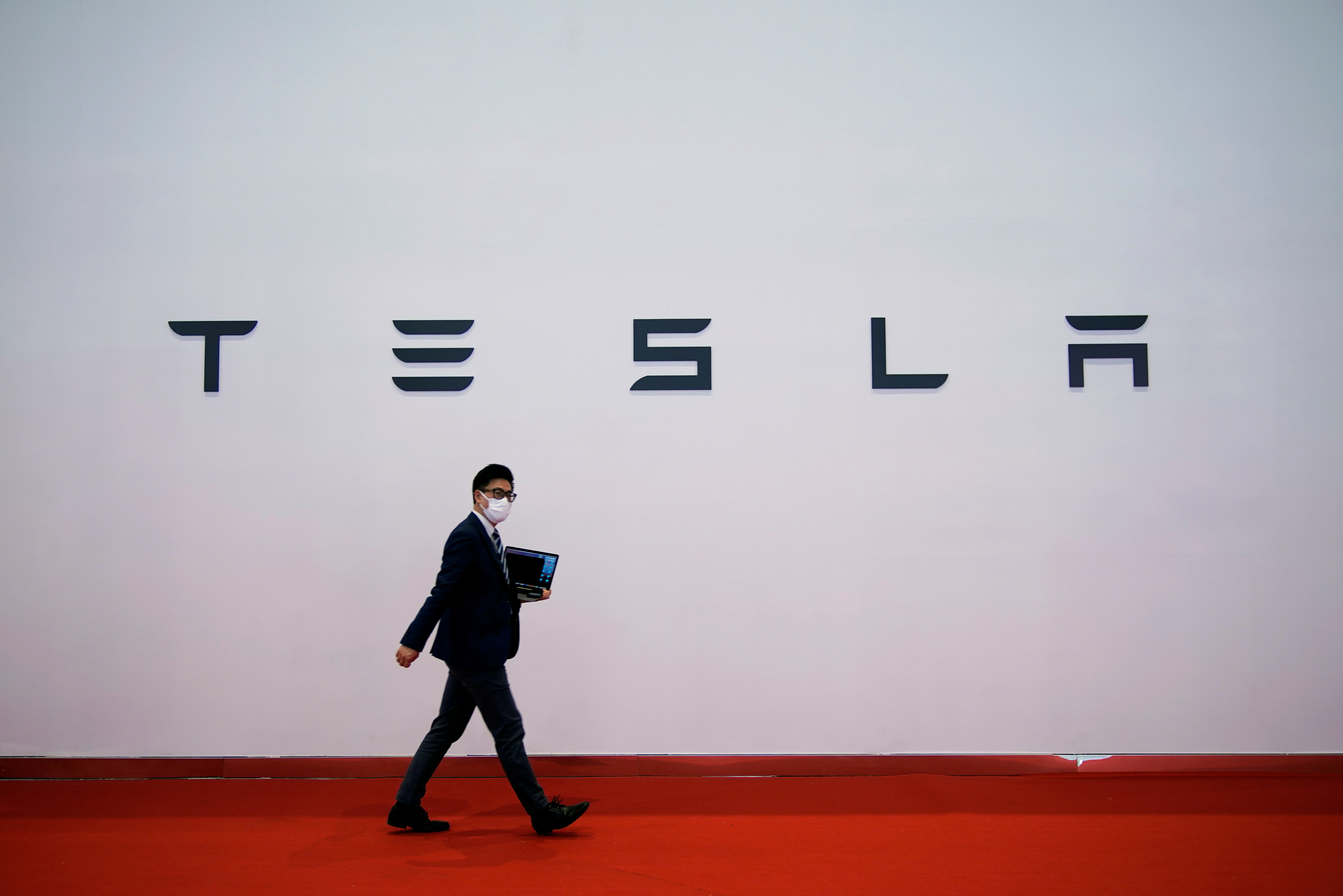 A man holding a computer walks past a sign of electric carmaker Tesla during a media day for the Auto Shanghai show in Shanghai, China April 20, 2021. REUTERS/Aly Song