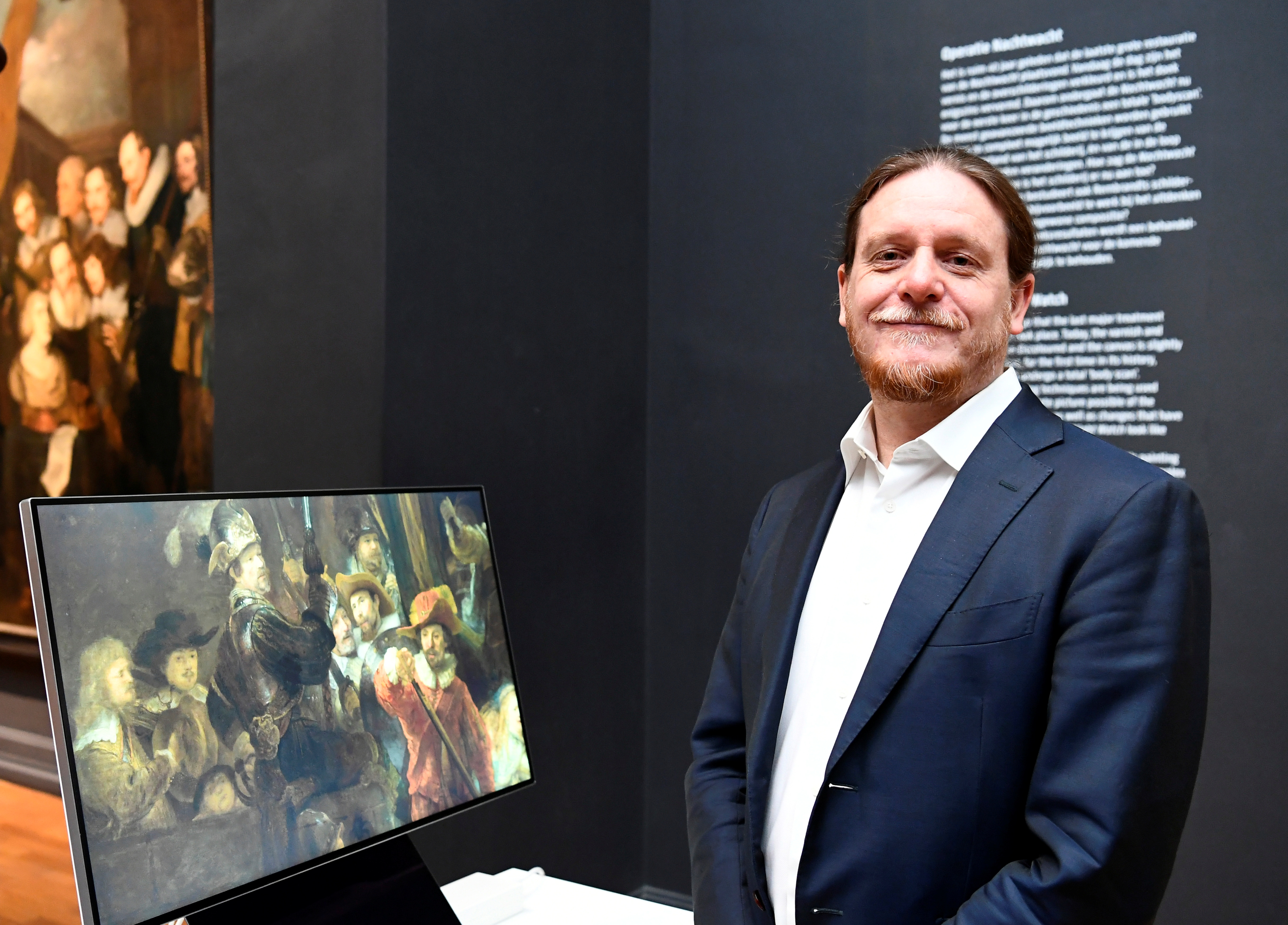 Robert Erdmann, senior scientist at the Rijksmuseum, shows Rembrandt's famed Night Watch on a screen, while the painting is back on display in what researchers say in its original size, with missing parts temporarily restored in an exhibition aided by artificial intelligence at Rijksmuseum in Amsterdam, Netherlands June 23, 2021. REUTERS/Piroschka van de Wouw