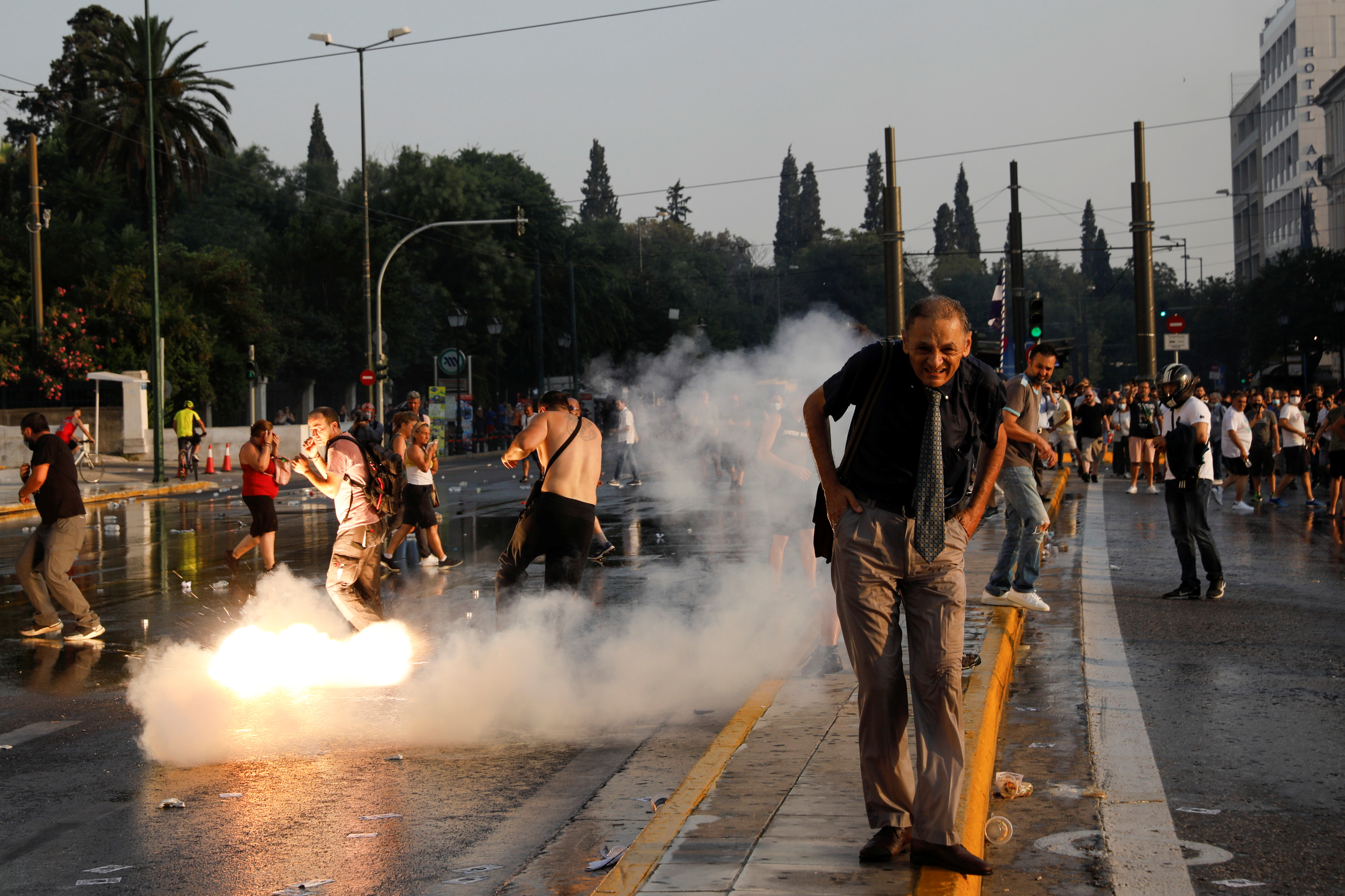 A man reacts as a flash grenade thrown by police officers explodes behind, during a protest againstcoronavirusdisease (COVID-19) vaccinations outside the parliament building, in Athens, Greece, July 21, 2021. REUTERS/Costas Baltas