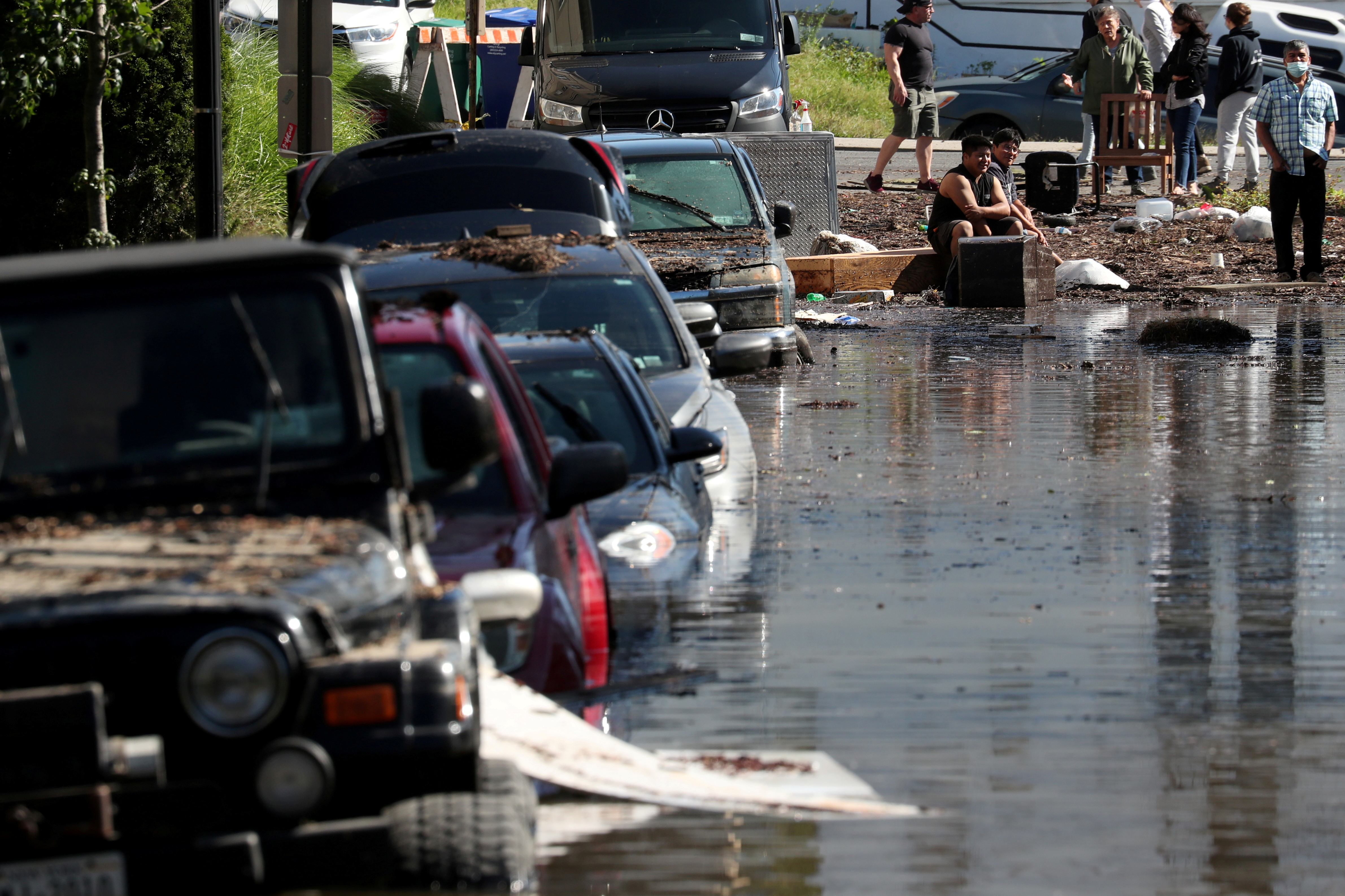 Local residents stand by floodwaters after remnants of Ida brought drenching rain, flash floods and tornadoes to parts of the Northeast in Mamaroneck, New York, September 2. REUTERS/Mike Segar