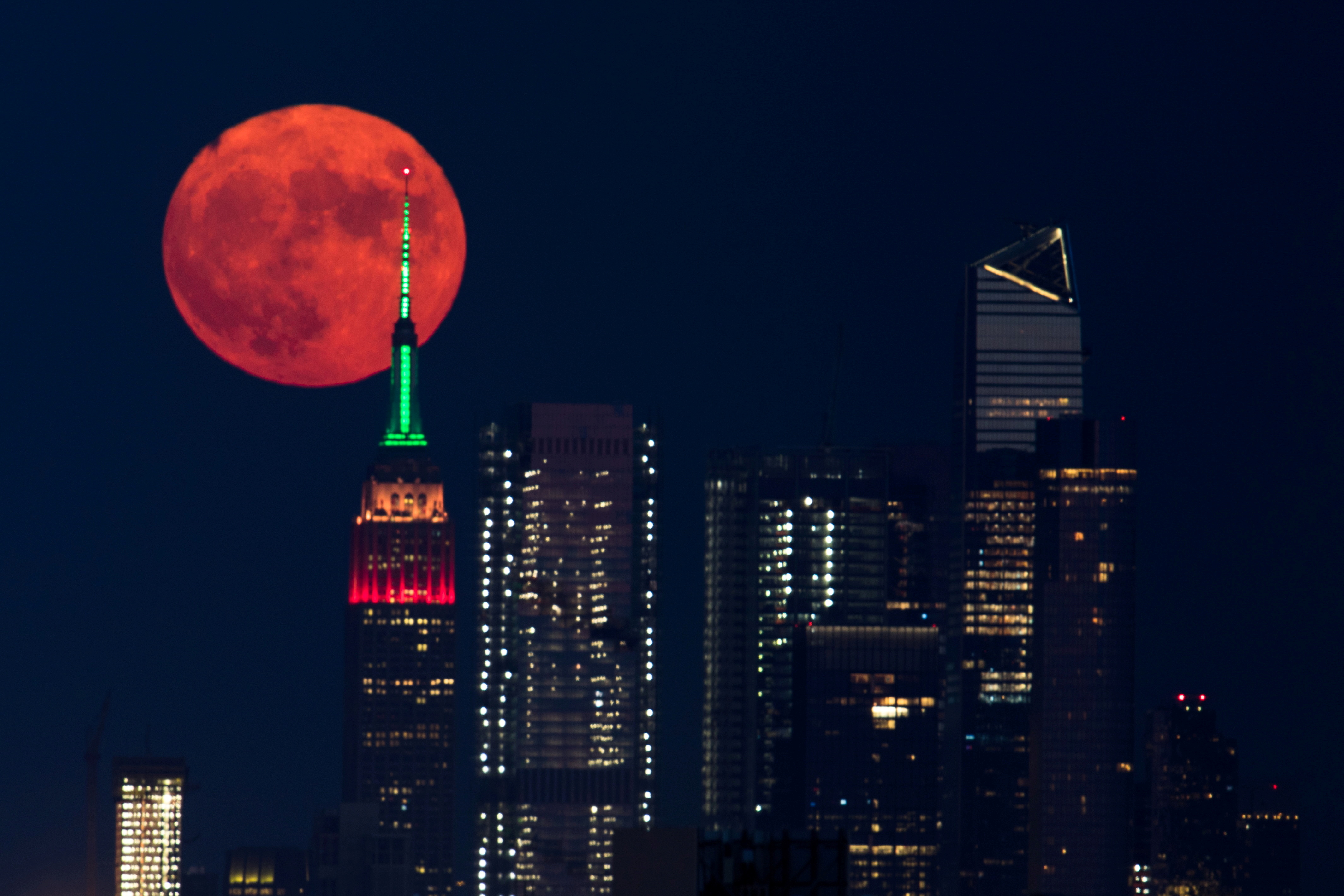 The full moon rises behind the Empire State Building in New York City, New York, U.S., July 23, 2021. REUTERS/Bjoern Kils/New York Media Boat