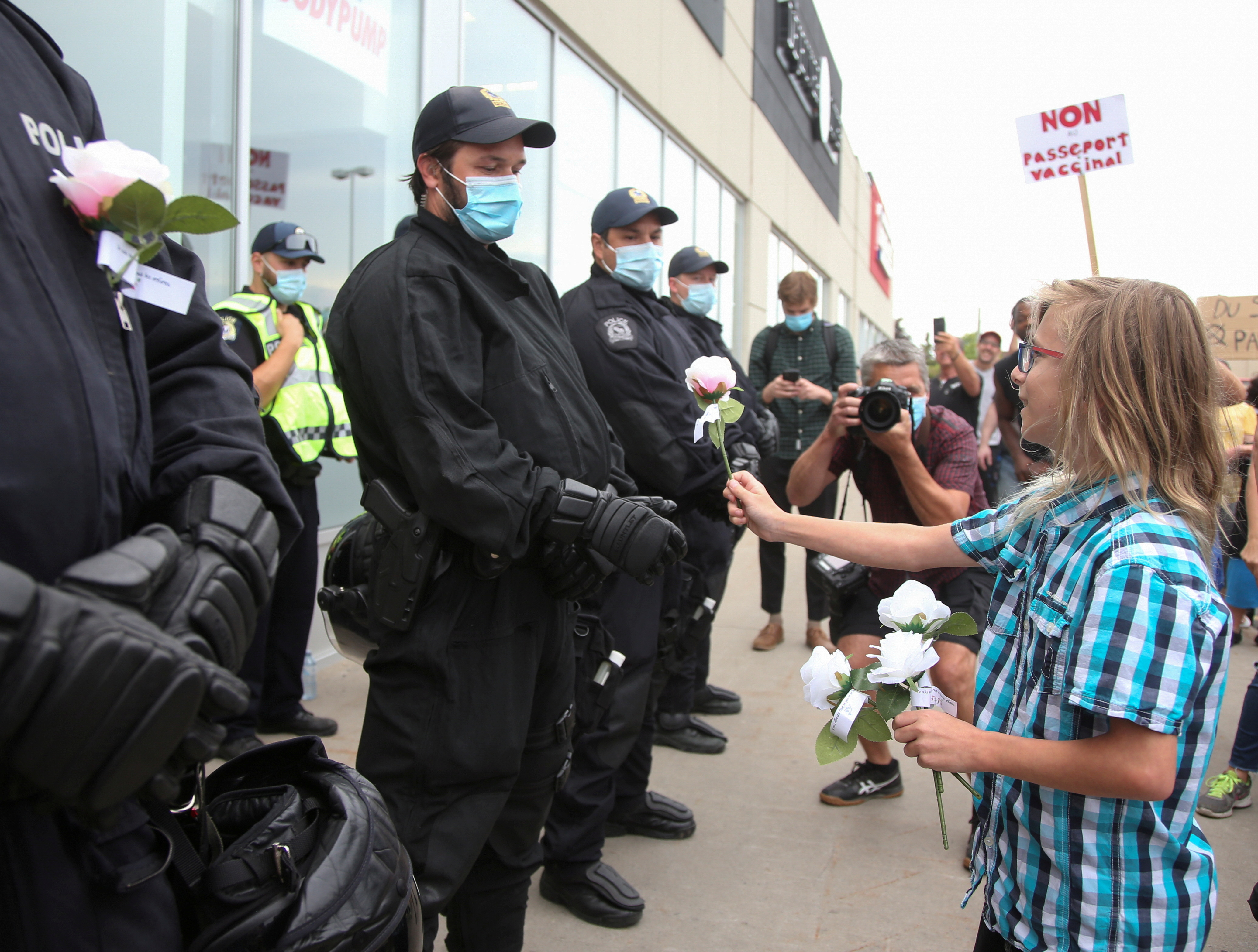 A protester gives roses to riot police members guarding the entrance to an Econofitness gym as people protest their use of a vaccine passport in Laval, Quebec, Canada August 17, 2021.  REUTERS/Christinne Muschi/File Photo