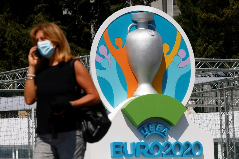 A woman wearing a protective mask walks past the logo of UEFA Euro 2020 at the fan zone at Piazza del Popolo in Rome, Italy, June 7, 2021. REUTERS/Guglielmo Mangiapane/File Photo