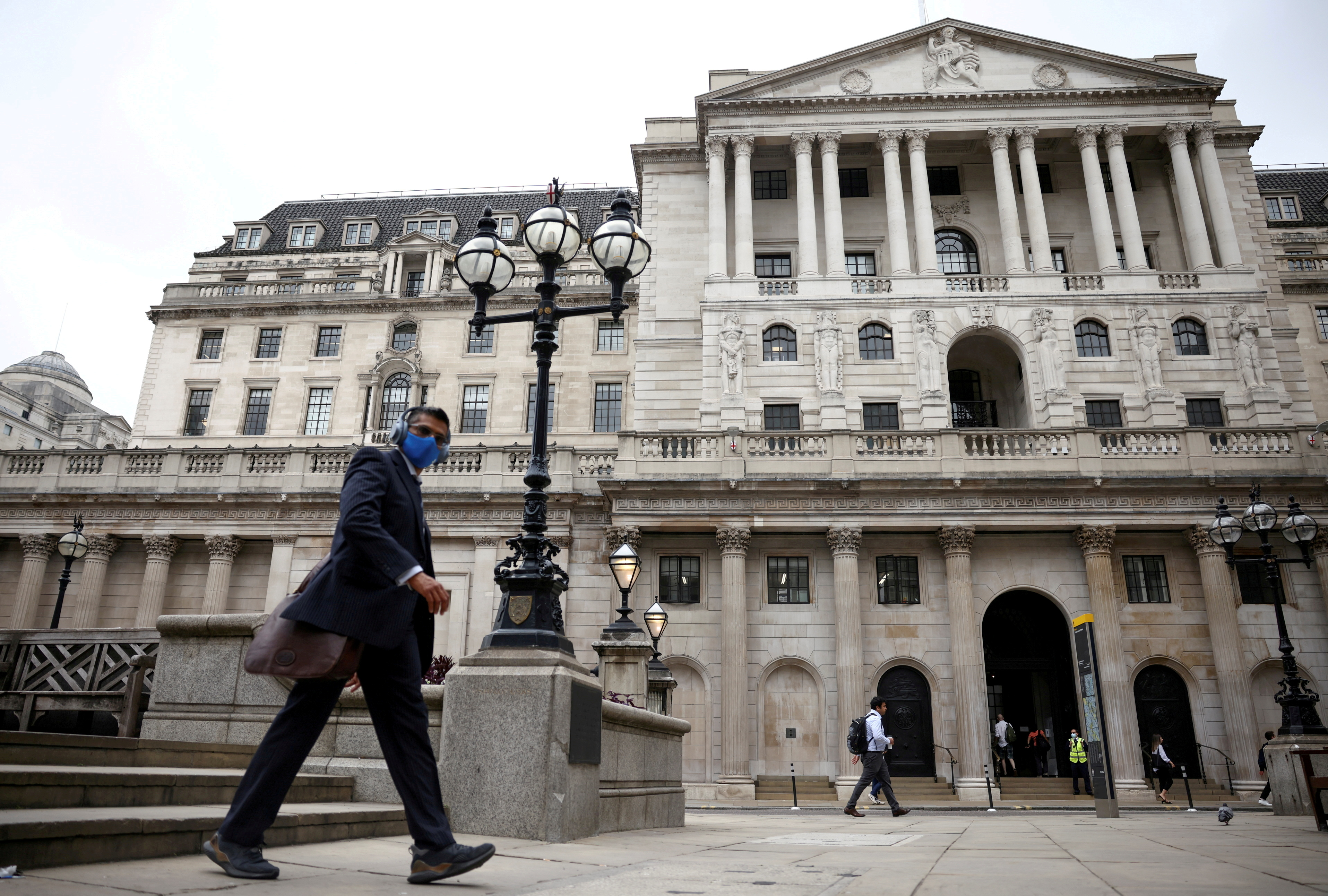A person walks past the Bank of England in the City of London financial district, in London, Britain, June 11, 2021. REUTERS/Henry Nicholls/File Photo