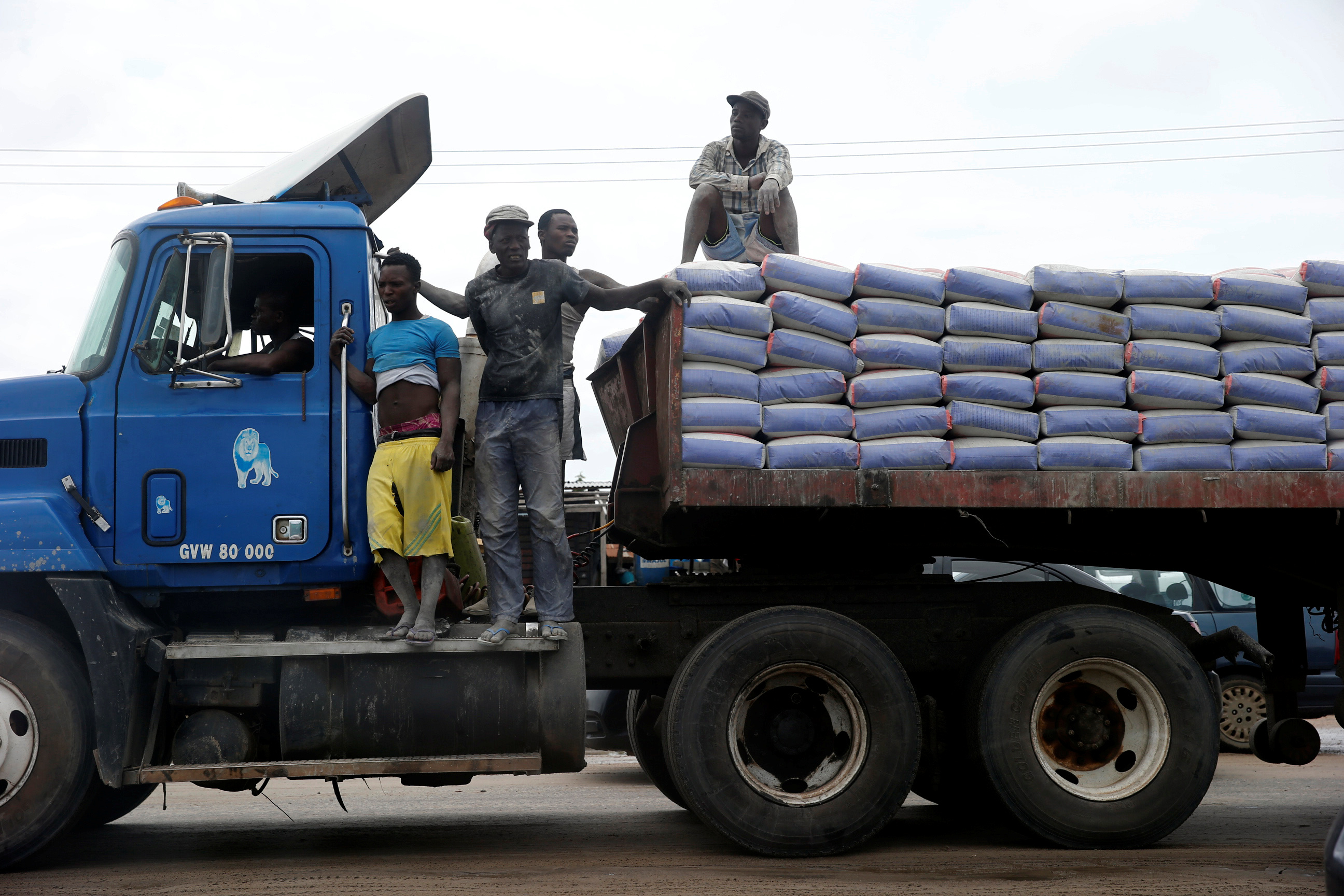 Labourers stand on top of a trailer transporting cement along Ajah-Lagos expressway in Nigeria's commercial capital Lagos, Nigeria June 3, 2017. REUTERS/Akintunde Akinleye
