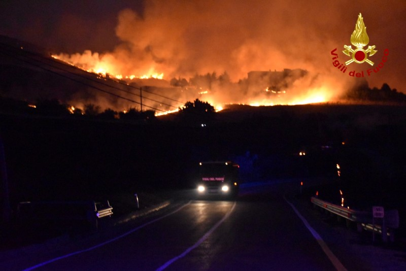 A hillside is engulfed in flames as a wildfire burns in Petralia Soprana, Italy August 10, 2021. Picture taken August 10, 2021. Vigili del Fuoco/Handout via REUTERS ATTENTION EDITORS THIS IMAGE HAS BEEN SUPPLIED BY A THIRD PARTY. DO NOT OBSCURE LOGO.