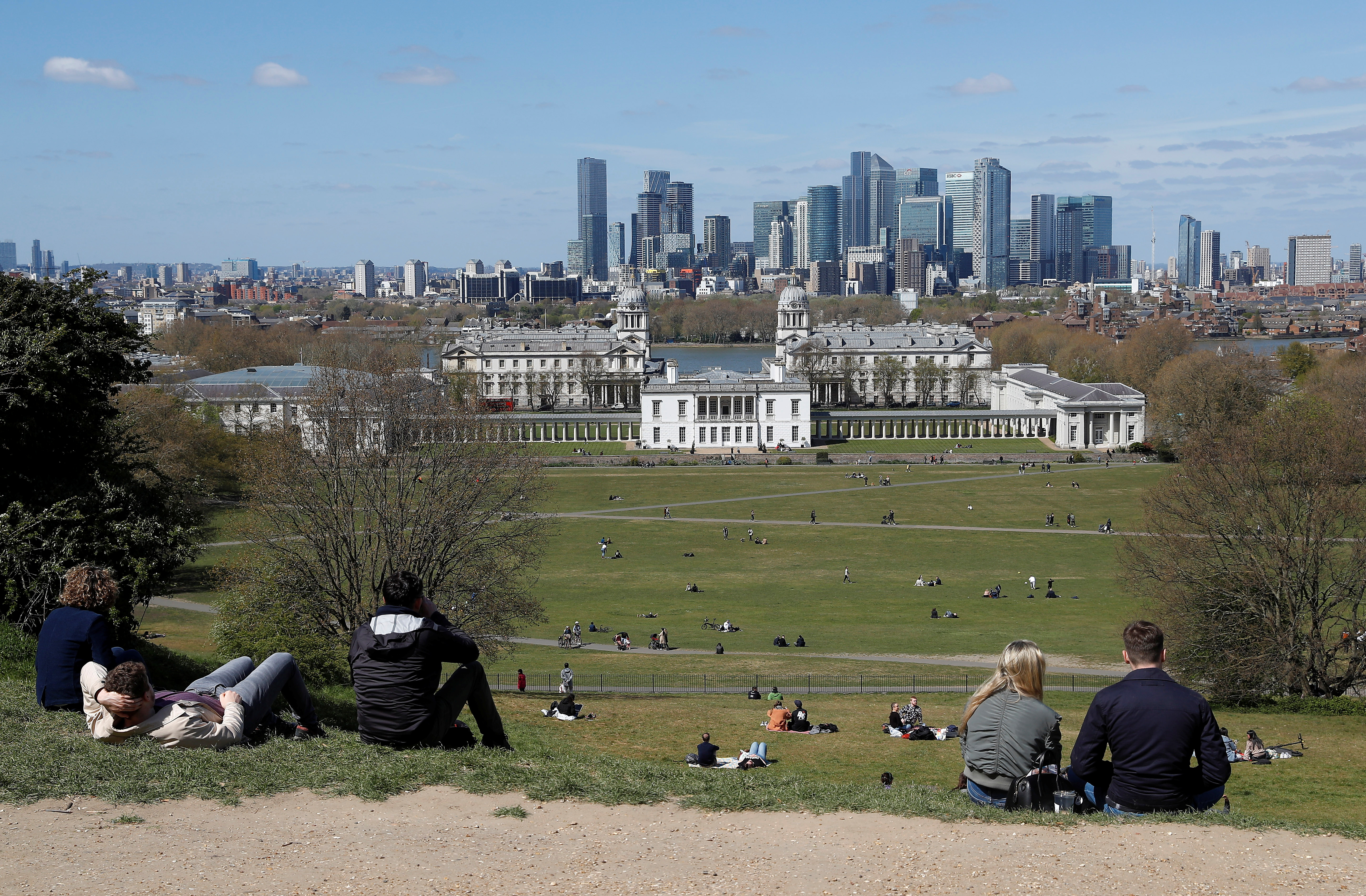 Visitors to Greenwich Park sit and look towards Canary Wharf financial district as lockdown restrictions are eased amidst the spread of the coronavirus disease (COVID-19) pandemic in London, Britain, April 25, 2021. REUTERS/Peter Nicholls