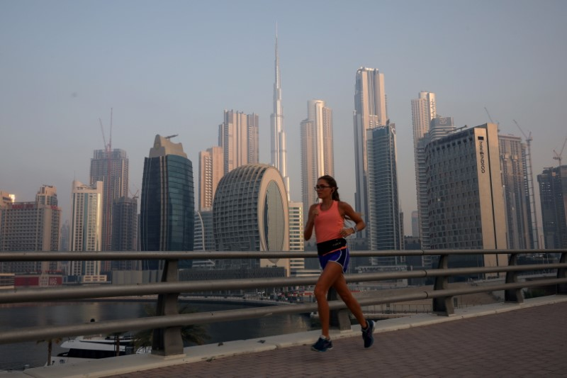 A woman runs past the Burj Khalifa and the downtown skyline in Dubai, United Arab Emirates, June 13, 2021. REUTERS/Christopher Pike