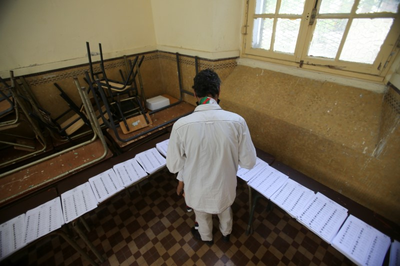 A voter looks at ballots at a polling station during the parliamentary election, in Algiers, Algeria June 12, 2021. REUTERS/Ramzi Boudina