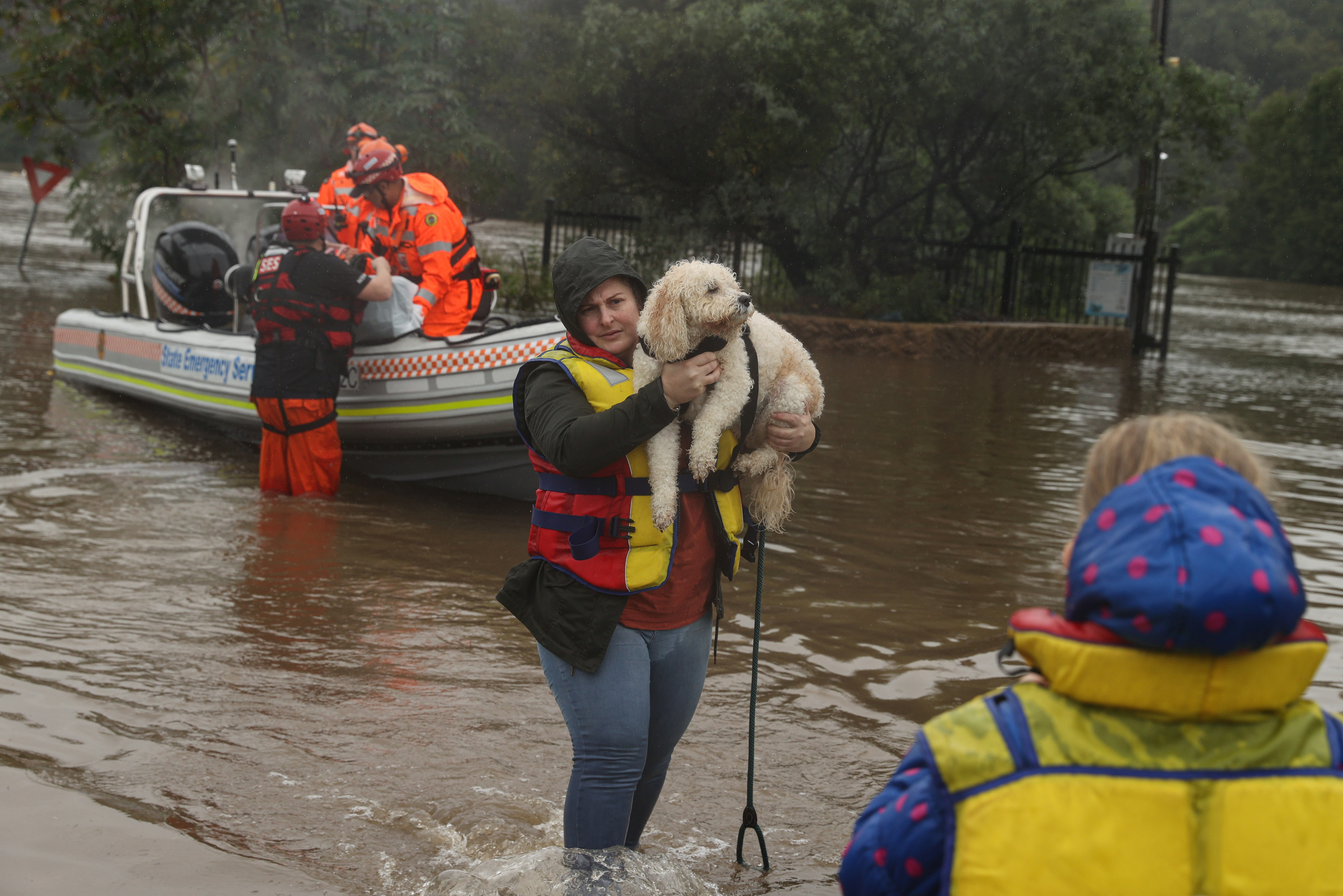 A woman and dog rescued by a State Emergency Service crew make it to safety after being trapped by rising floodwaters, as the state of New South Wales experiences widespread flooding and severe weather, in the suburb of Sackville North in Sydney, Australia, March 23, 2021.  REUTERS/Loren Elliott