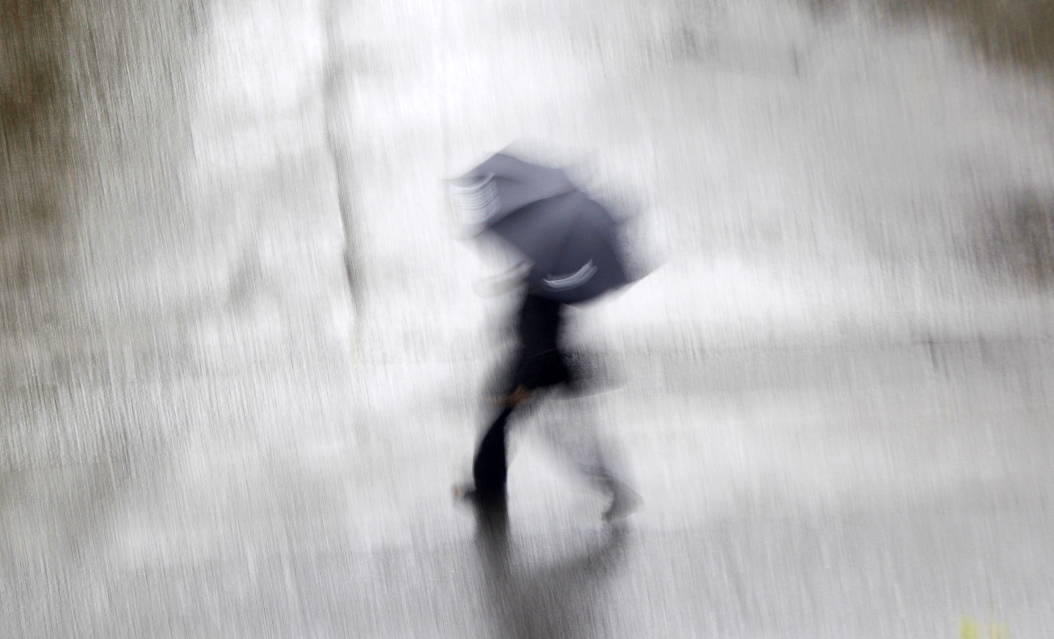A man with an umbrella crosses a road in central Sydney February 6, 2010. REUTERS/Tim Wimborne