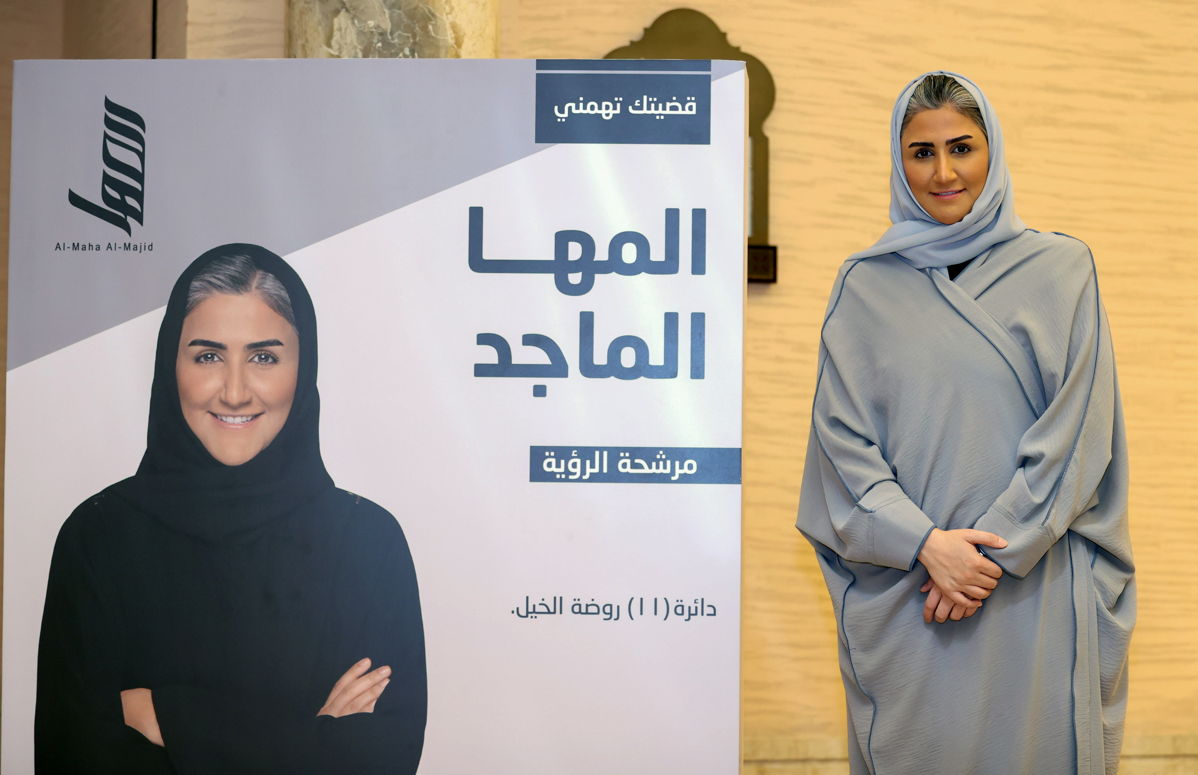 Al-Maha Al-Majid, a candidate in Qatar's Shura Council election, poses for a photo next to an election poster in Doha, Qatar September 30, 2021. REUTERS/Ibraheem Al Omari