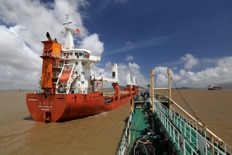 A Sinopec oil tanker approaches cargo vessel Dongtai Baoze (L) berthed at an anchorage off Zhoushan port to supply it with bunker fuel, in Zhejiang province, China August 14, 2018. Picture taken August 14, 2018. REUTERS/Stringer/File photo