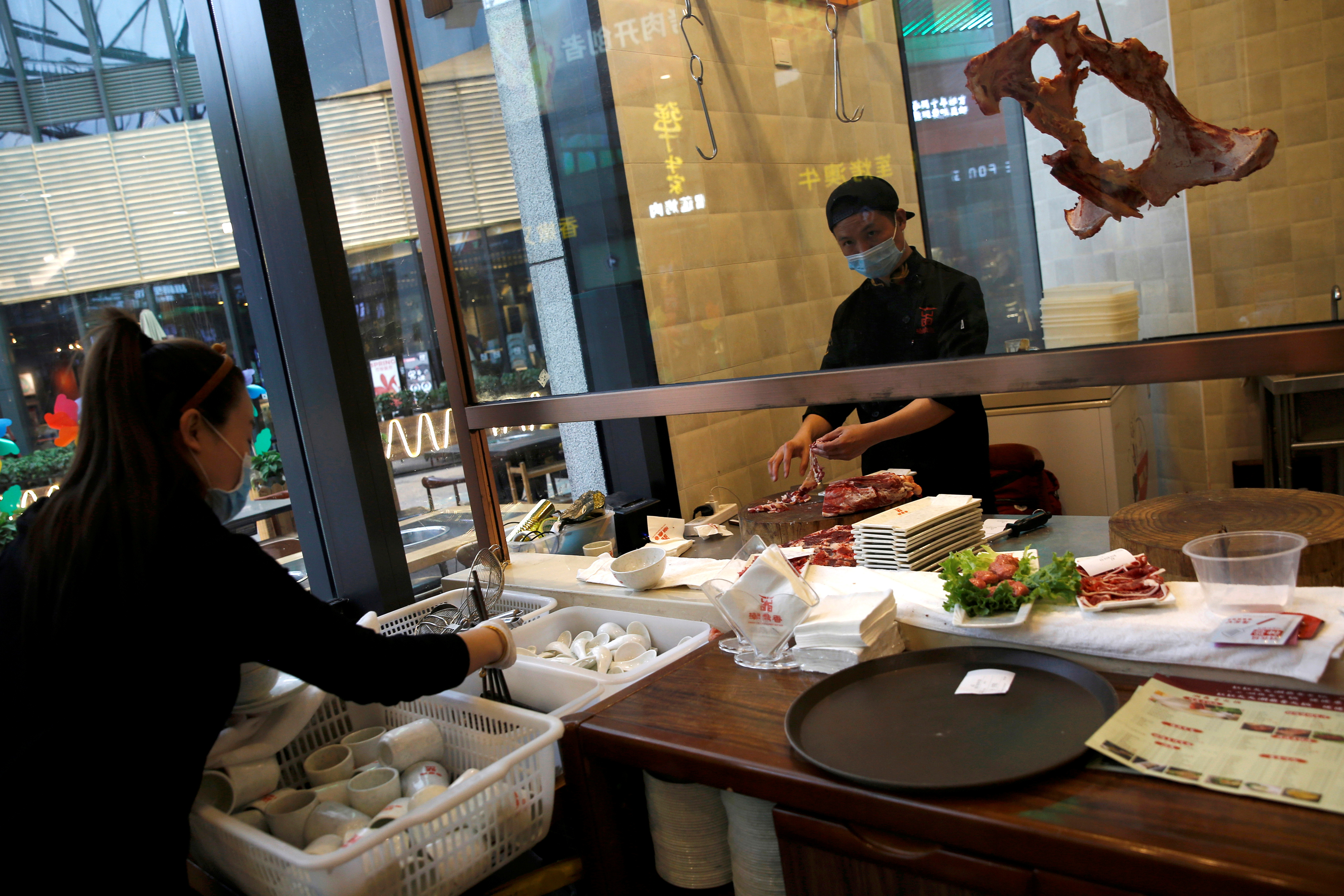 A chef wearing a face mask prepares beef as a waitress sorts tableware at a beef hotpot restaurant in Beijing, amid an outbreak of the novel coronavirus disease (COVID-19) in the country, China April 7, 2020. REUTERS/Tingshu Wang/File Photo