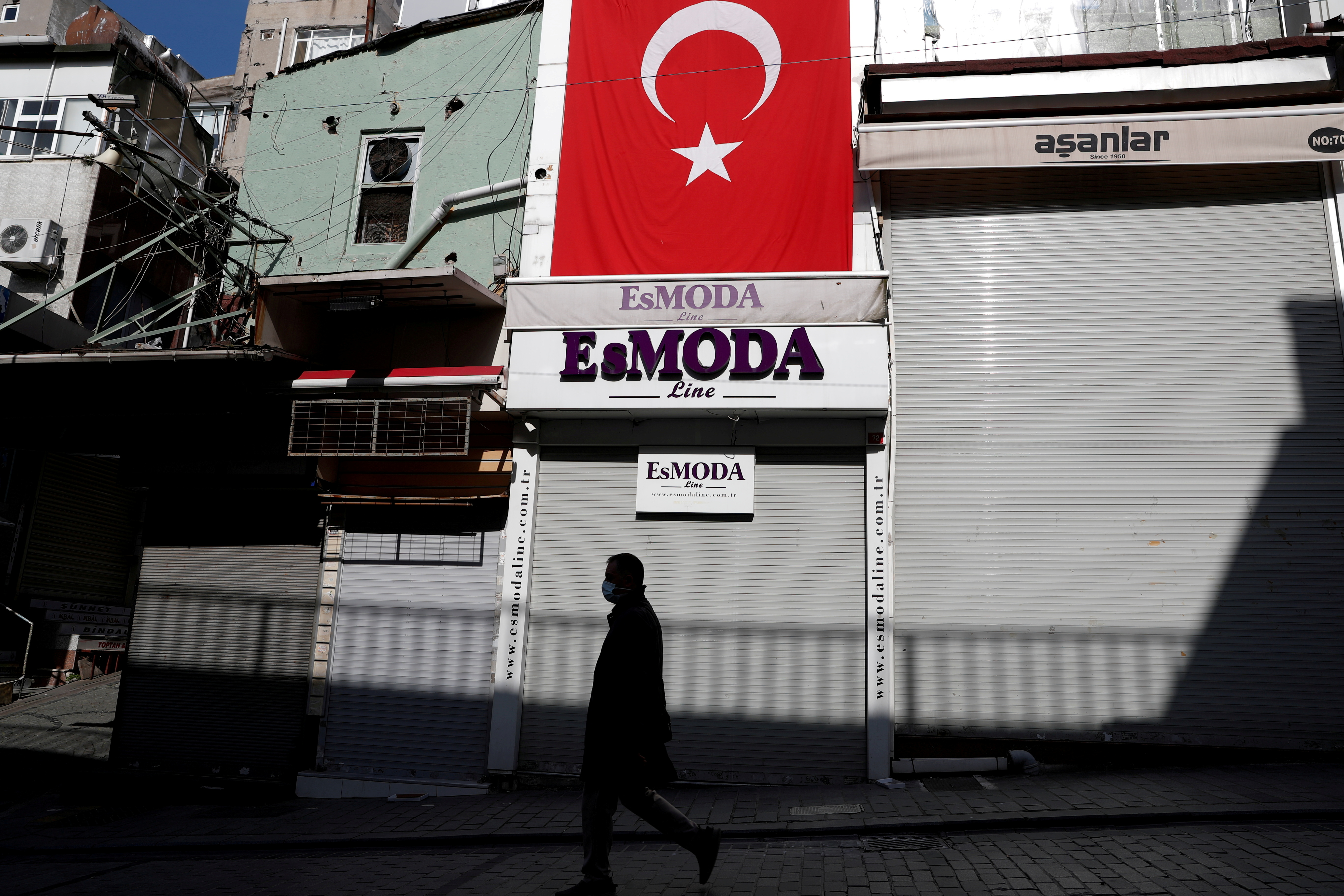 A man walks past by closed shops during a nationwide