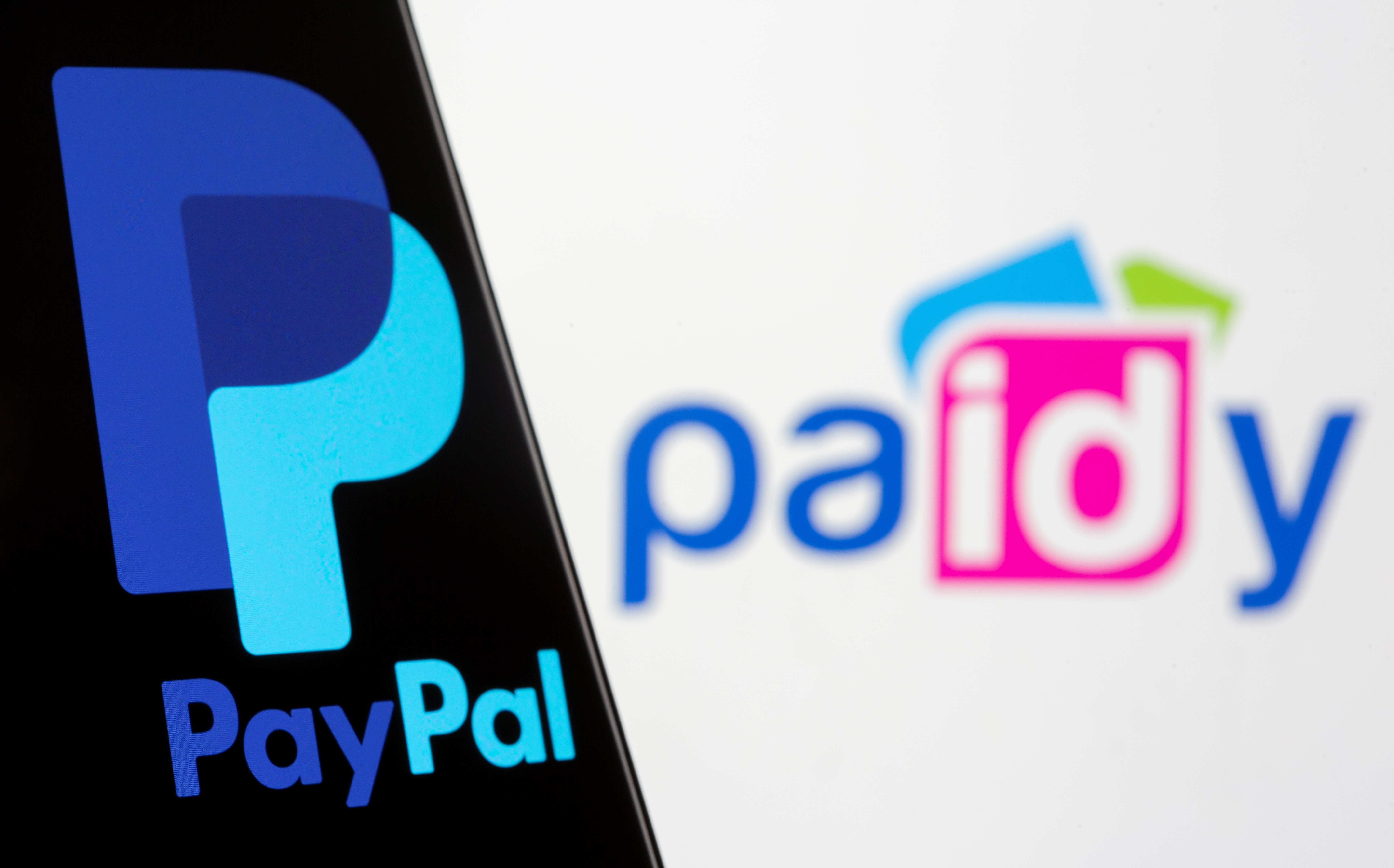 The PayPal logo is seen on a smartphone in front of a displayed Paidy logo in this illustration taken September 8, 2021. REUTERS/Dado Ruvic/Illustration