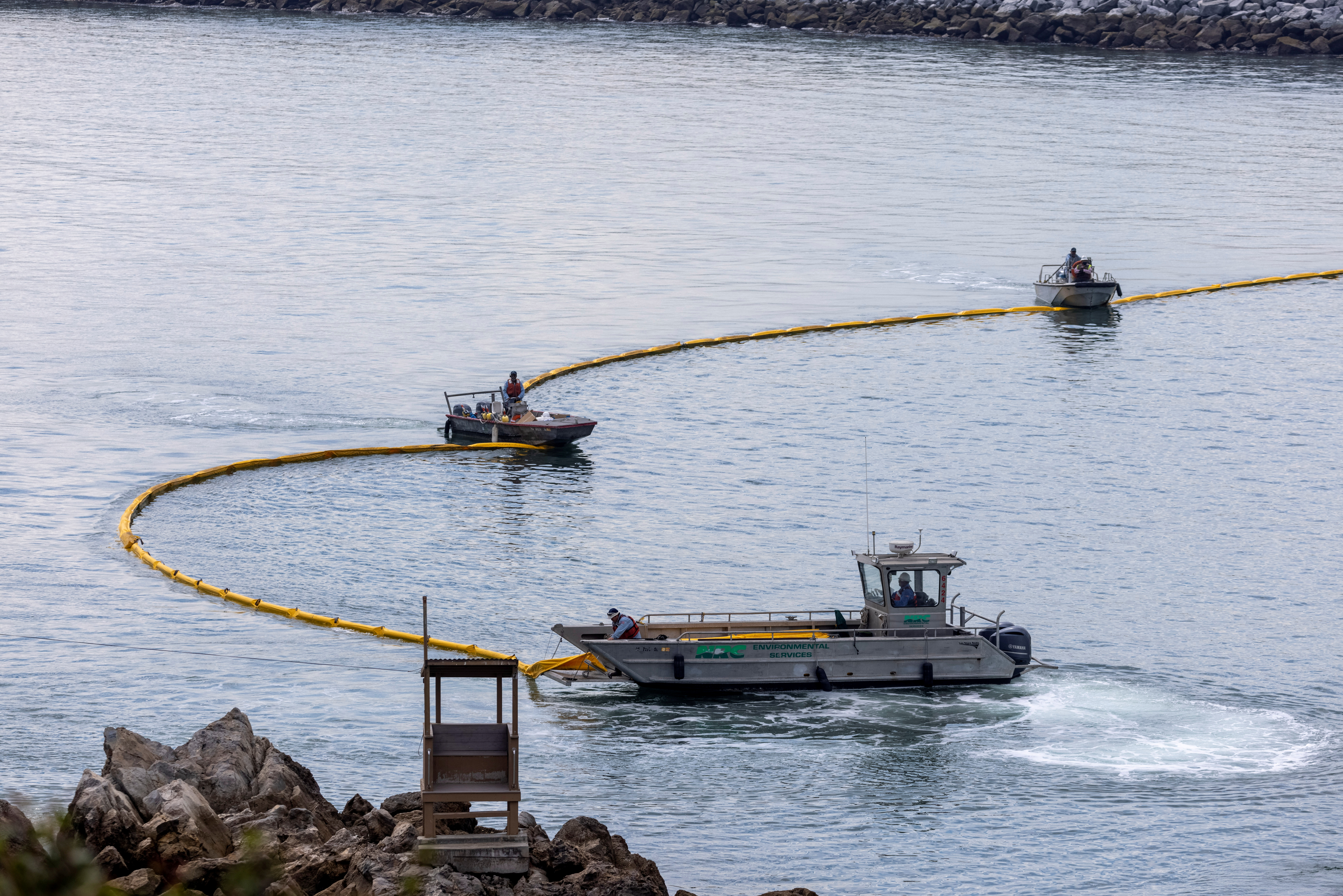 Workers seal off the entrance to Newport Beach harbor as a major oil spill off the coast of California travels south in ocean currents, towards Newport Beach, California, U.S., October 4, 2021. REUTERS/Mike Blake/File Photo