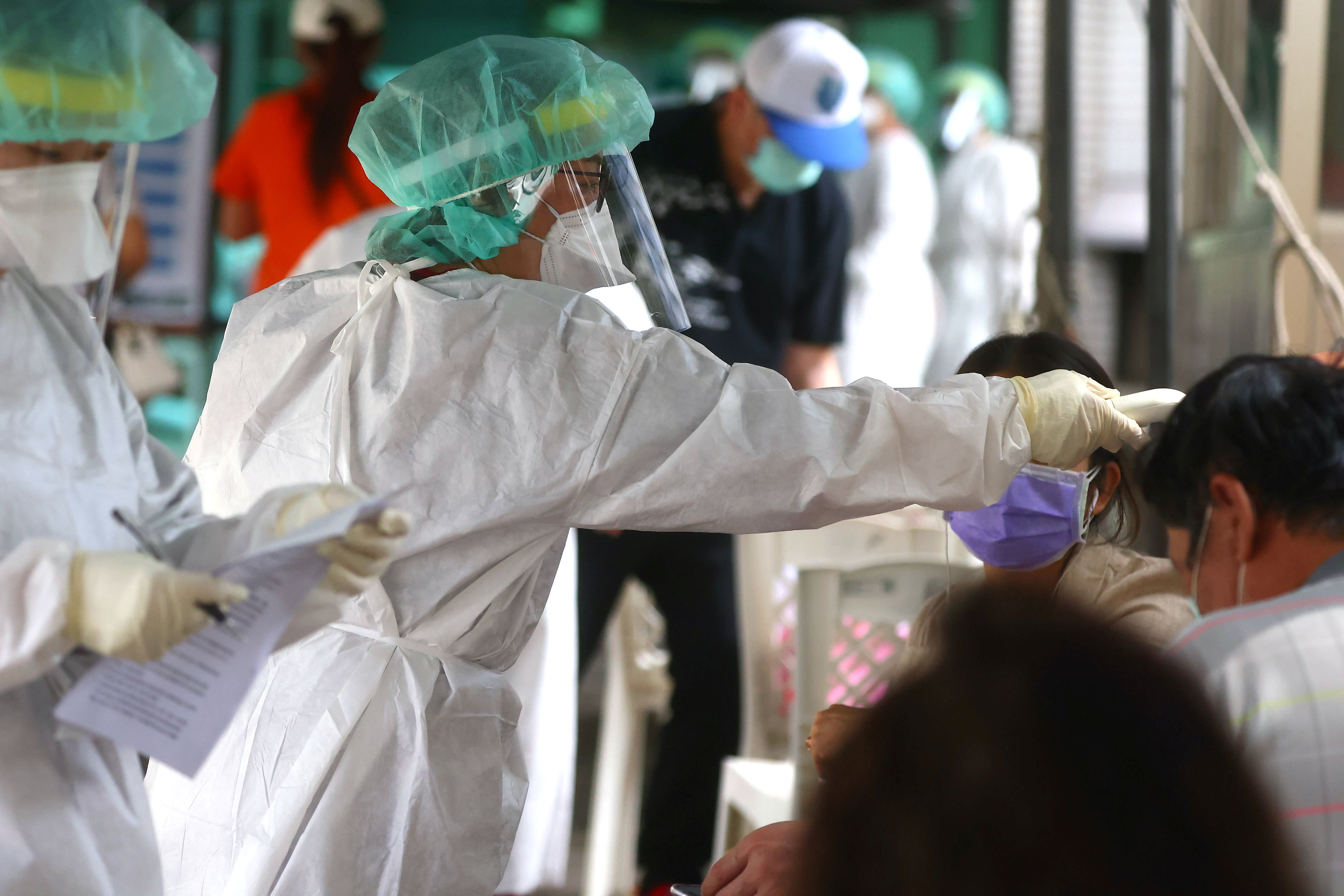 A healthcare frontline worker prepares people to get their rapid test following a surge of coronavirus disease (COVID-19) infections in Taipei, Taiwan May 17, 2021. REUTERS/Ann Wang