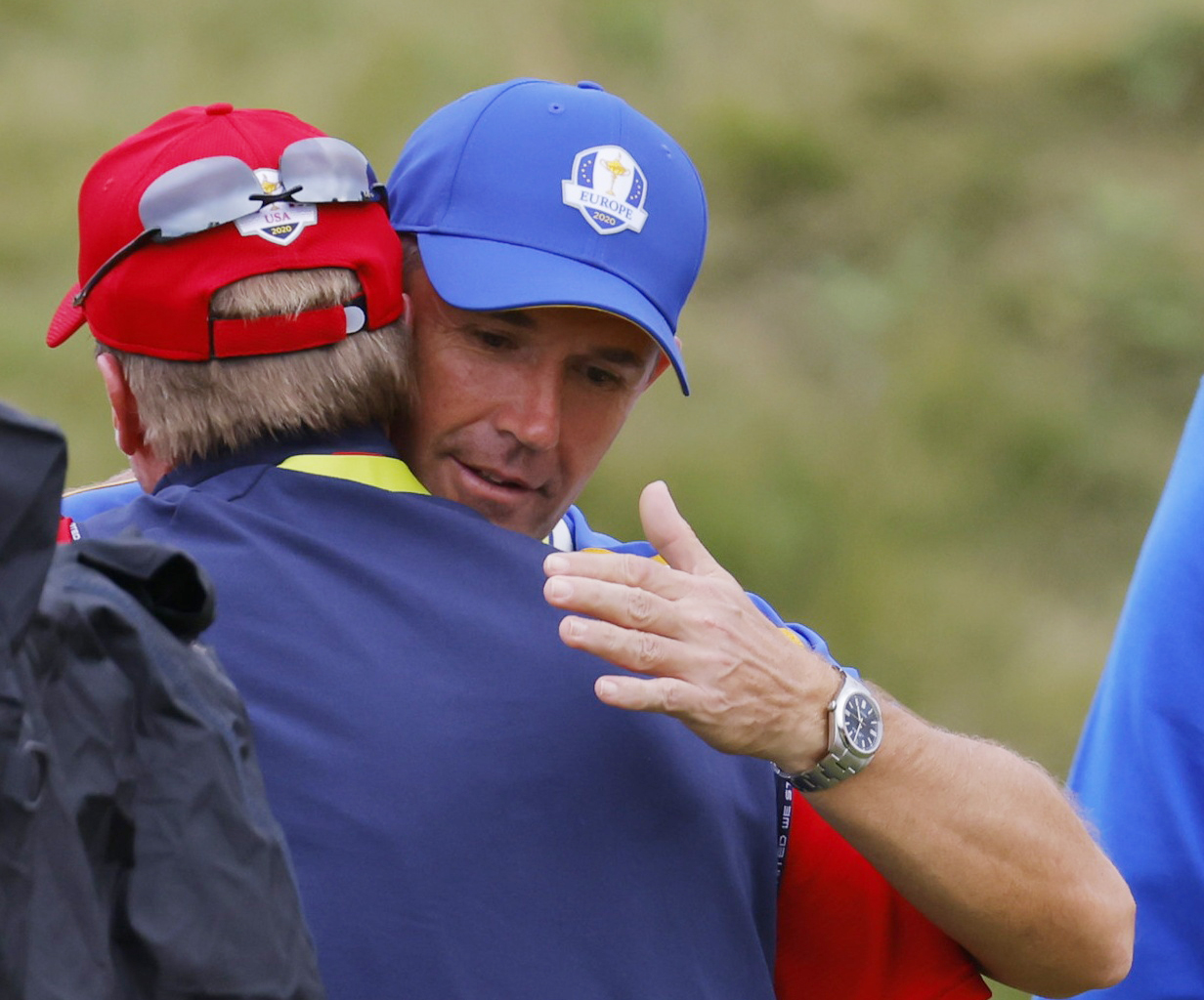 Golf - The 2020 Ryder Cup - Whistling Straits, Sheboygan, Wisconsin, U.S. - September 26, 2021 Team Europe captain Padraig Harrington congratulates Team USA captain Steve Stricker on the 18th hole after Team USA win the Ryder Cup REUTERS/Mike Segar/File photo