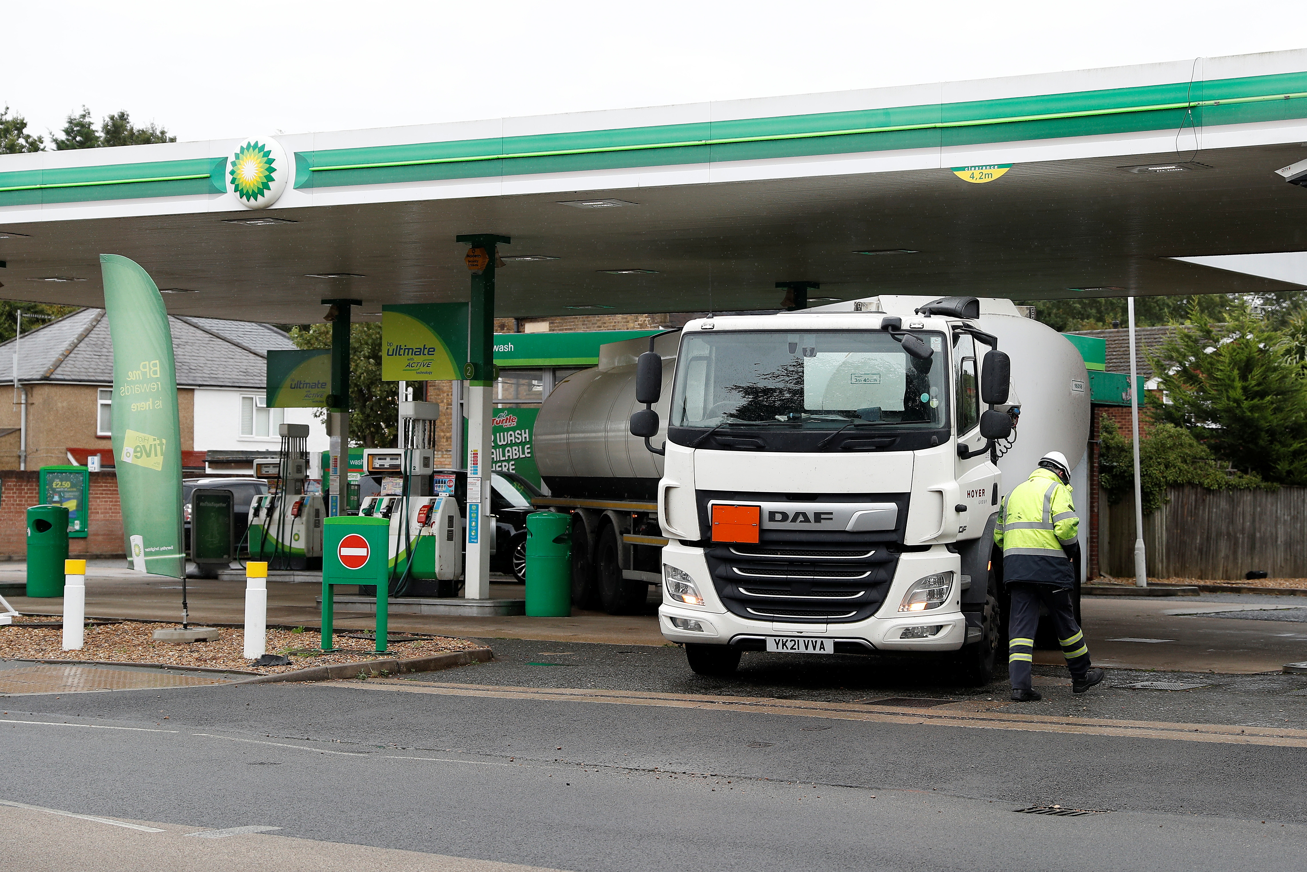 A driver walks past his tanker after completing a fuel delivery to a BP filling station in Hersham, Britain, September 30, 2021. REUTERS/Peter Nicholls